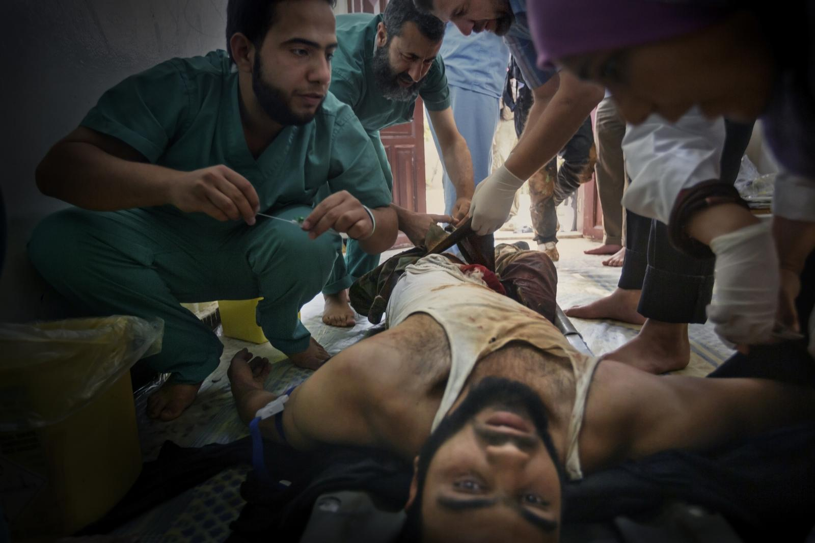A man is treated for serious injuries from a mortar attack on the floor at the entrance to a makeshift hospital. The same day, there were 27 injured and 5 dead in Al Qasir Hospital (Homs province), where only one of the 20 staff members was a doctor (Syria, 2012)