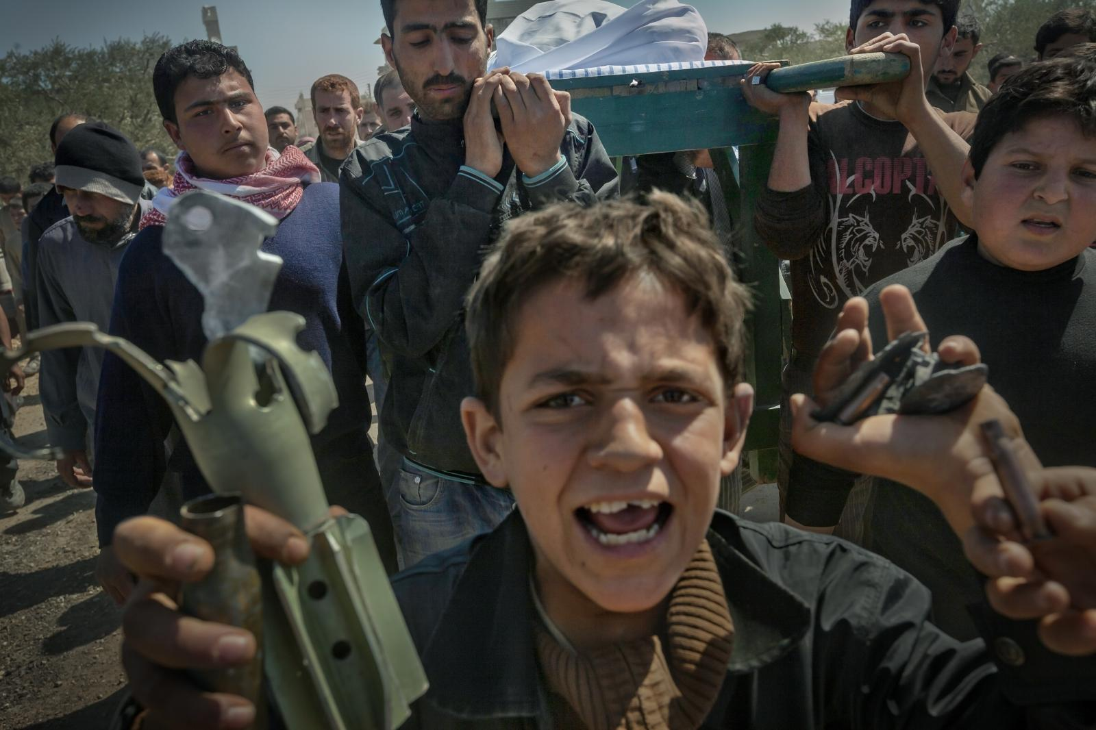 A boy hold s fragments of shrapnel shells from bombings by Assad ' s troops . Meanwhile , a funeral procession with the body of one of the victims killed in this attack follows him .Sermen ,Idlib province (Syria,2012)