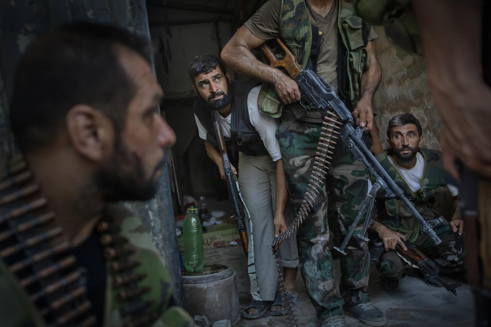 Free Syrian Army (FSA) soldiers during intense fighting against Assad's troops over the taking of the police station in the Old City of Aleppo. As a helicopter bombs the area, a soldier looks s up ( Syria , 2012 )