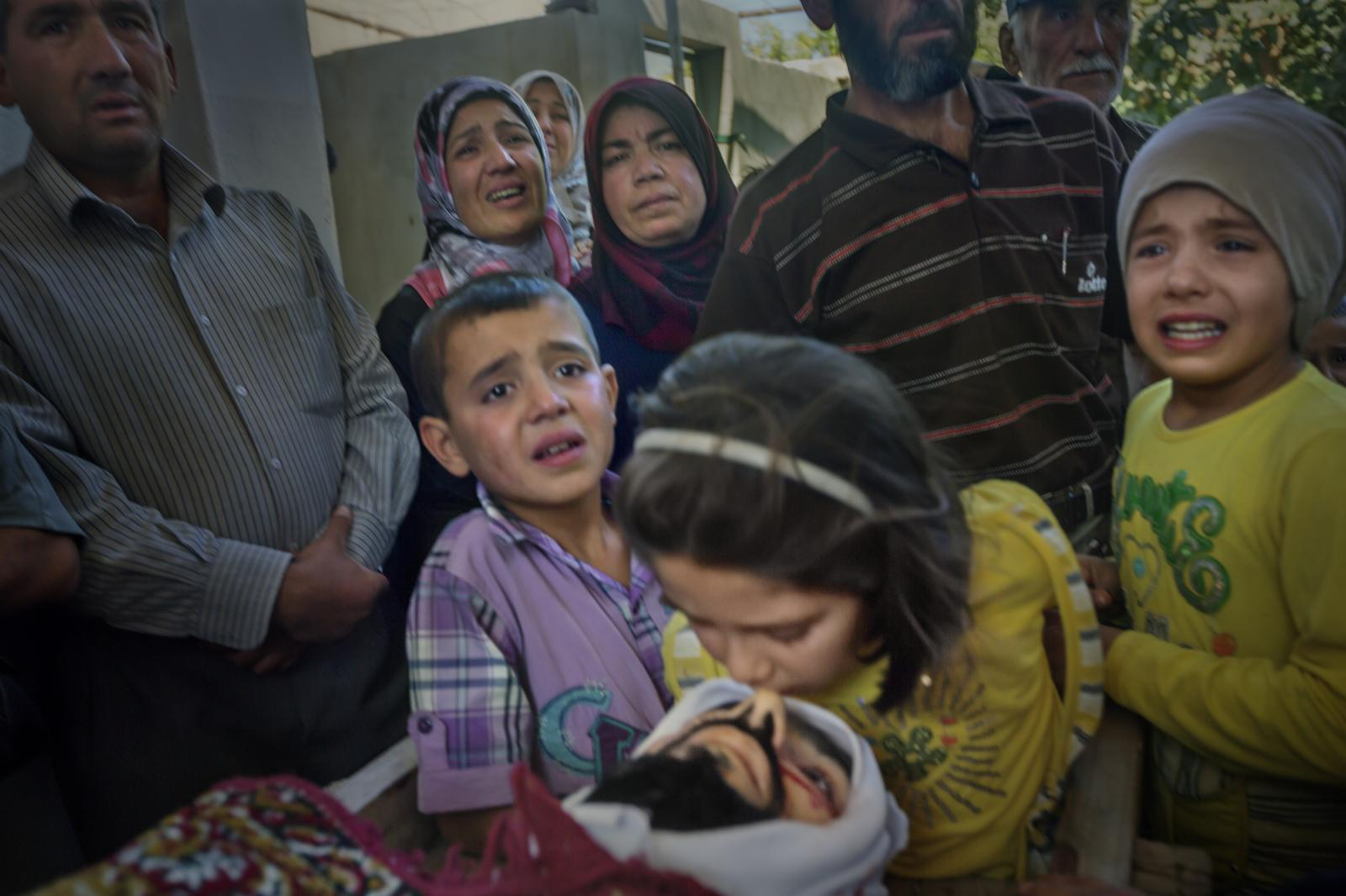 A 5 - year - old girl kisses the corpse of her father , Khaled Kasem Aleiter , killed today by a mortar shell that fell while he was crossing the street in the city of Al Qasir. His other two children and his wife cry over their loss (Syria, 2012)