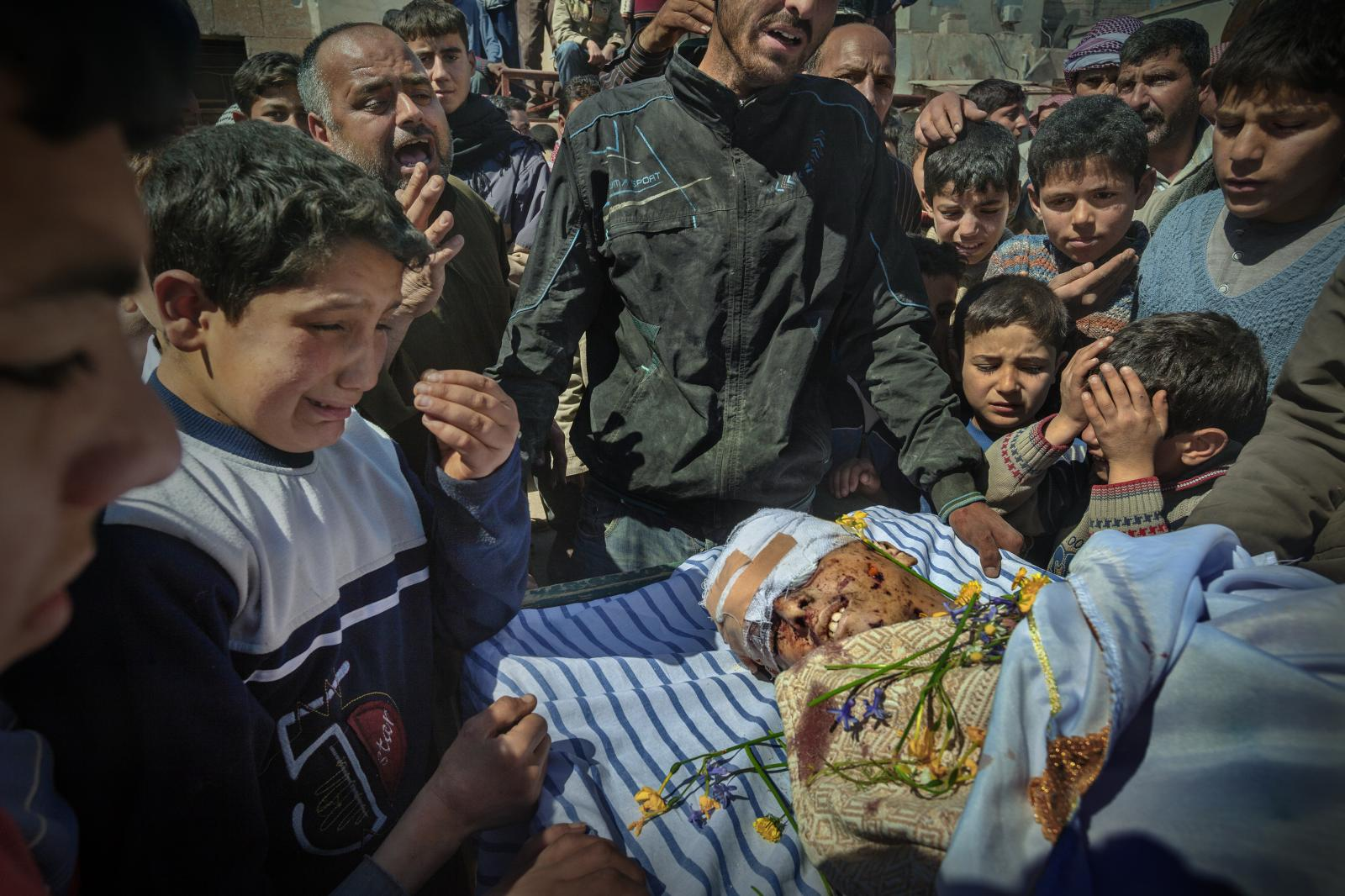 Ahmad Benmushen Qaruosh , 13 years old , died Thursday from the bombing b y Assad ' s troops in Sermen , Idlib province . Shrapnel from a tank shell riddled his body.His grief-stricken brother weeps alongside him (Syria,2012)
