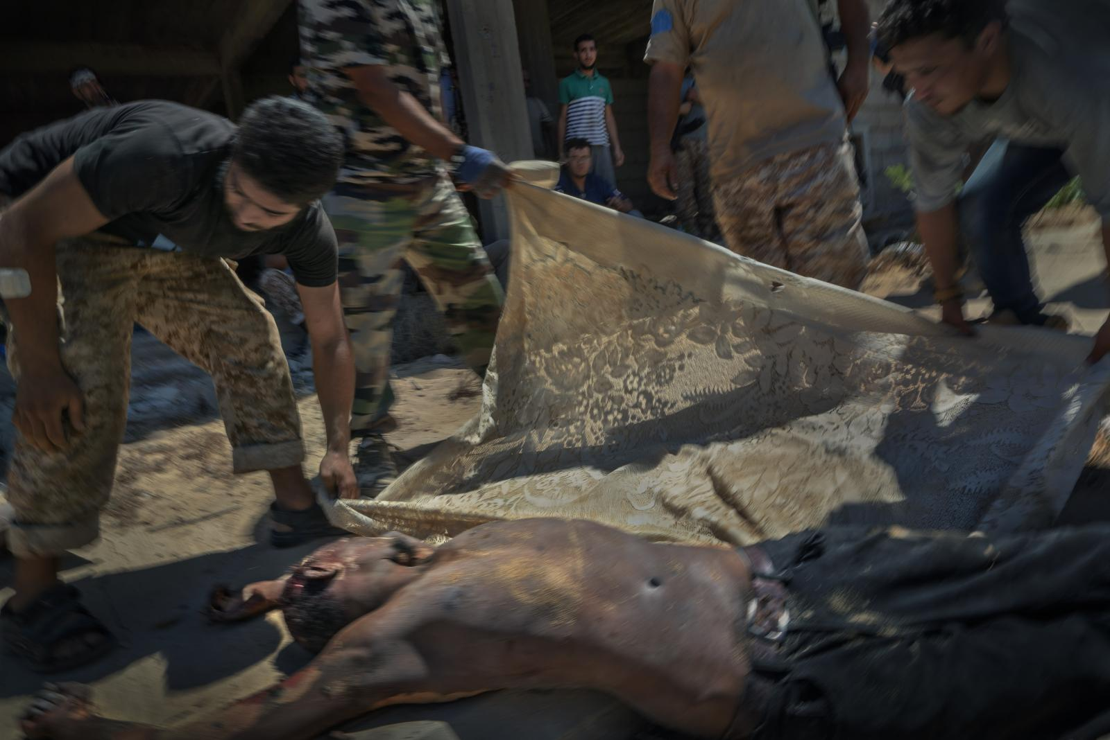 Fighters of the Government of National Accord (GNA), an interim government endorsed by the United Nations, cover the corpse of an ISIS militant in District 2. A large number of sub-Saharan Africans were among the ranks of ISIS in Sirte. Many of them neither understood Arabic nor, as a result, could read the Koran (Libya, 2016)