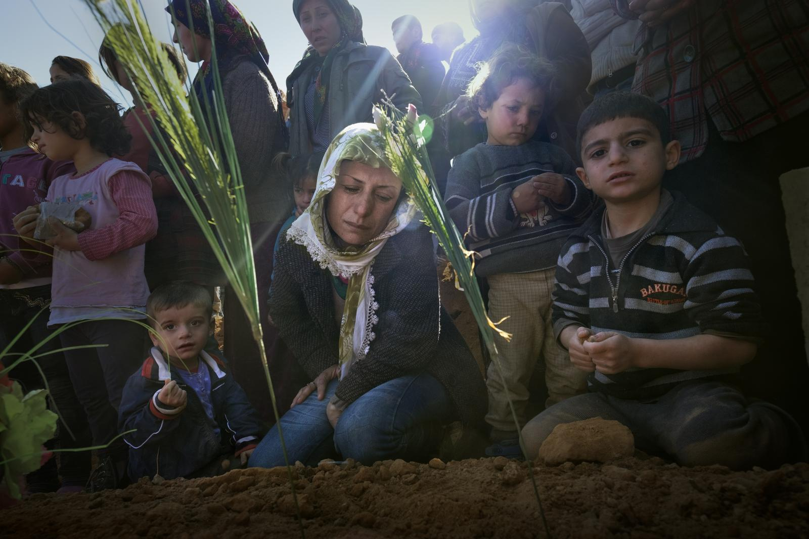 A Kurdish woman and her children weep alongside the grave of her husband , killed in the fighting to liberate the city of Kobane (Syria, 2015)