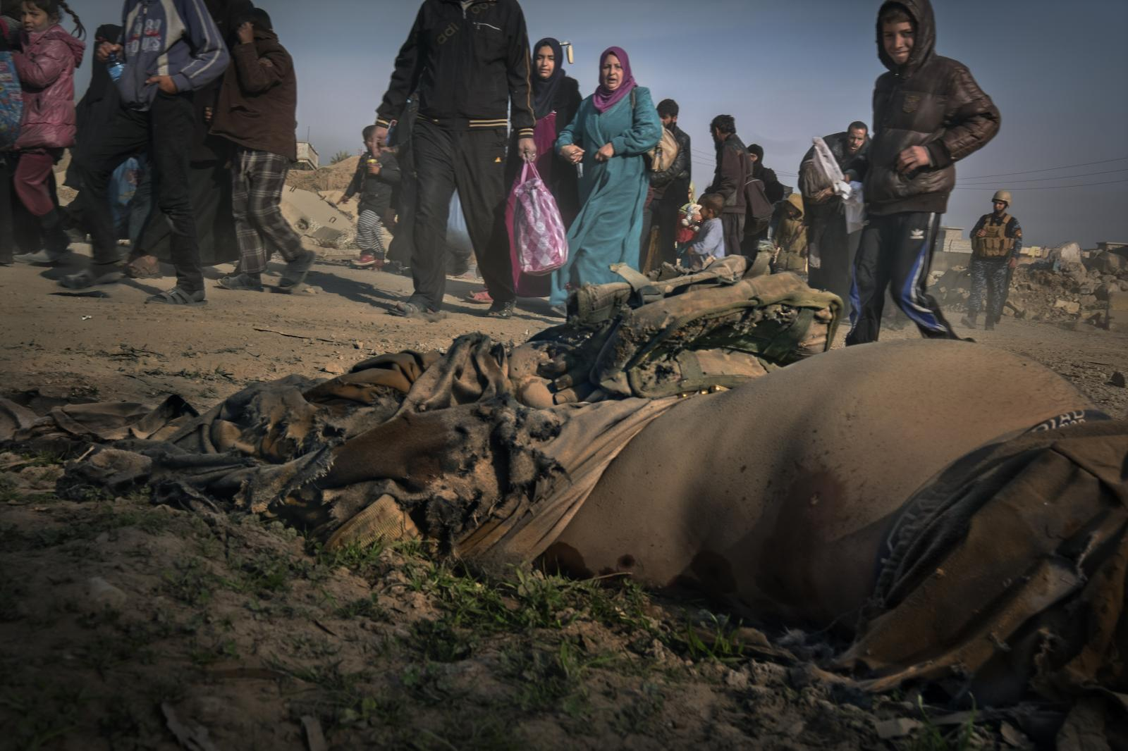 The corpse of an ISIS jihadist lies on the ground while refugees from Mosul attempt to escape escorted by the Federal Police ( elite units of the Iraqi Security Forces ) with the few belongings they still have, taking the road to the airport (Iraq, 2017)