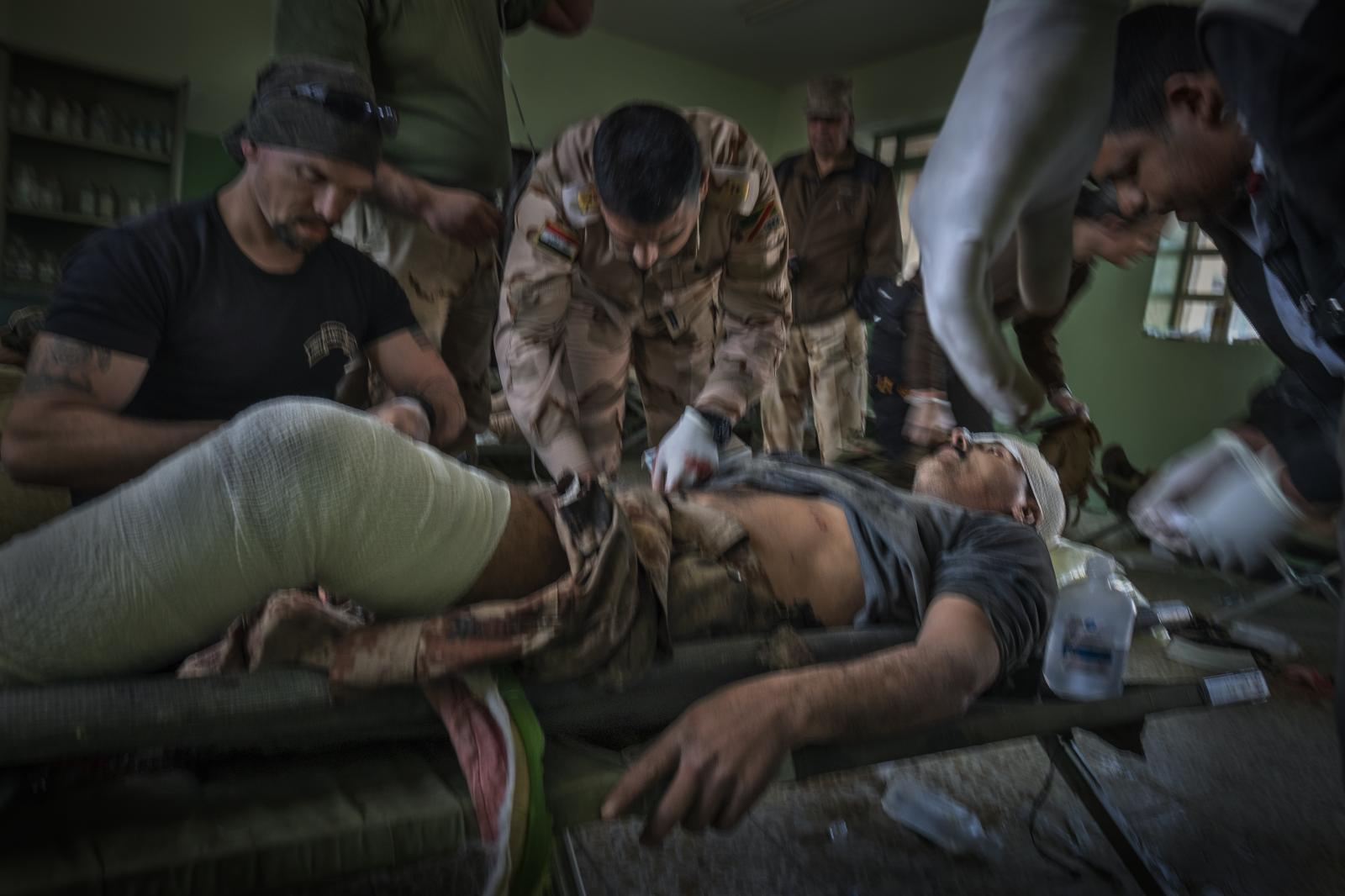 Members of the Free Burma Rangers (a multiethnic humanitarian service movement) assist Iraqi healthcare workers with several people injured in the fighting, in a field hospital on the southwestern front. Battle of Mosul (Iraq, 2017)
