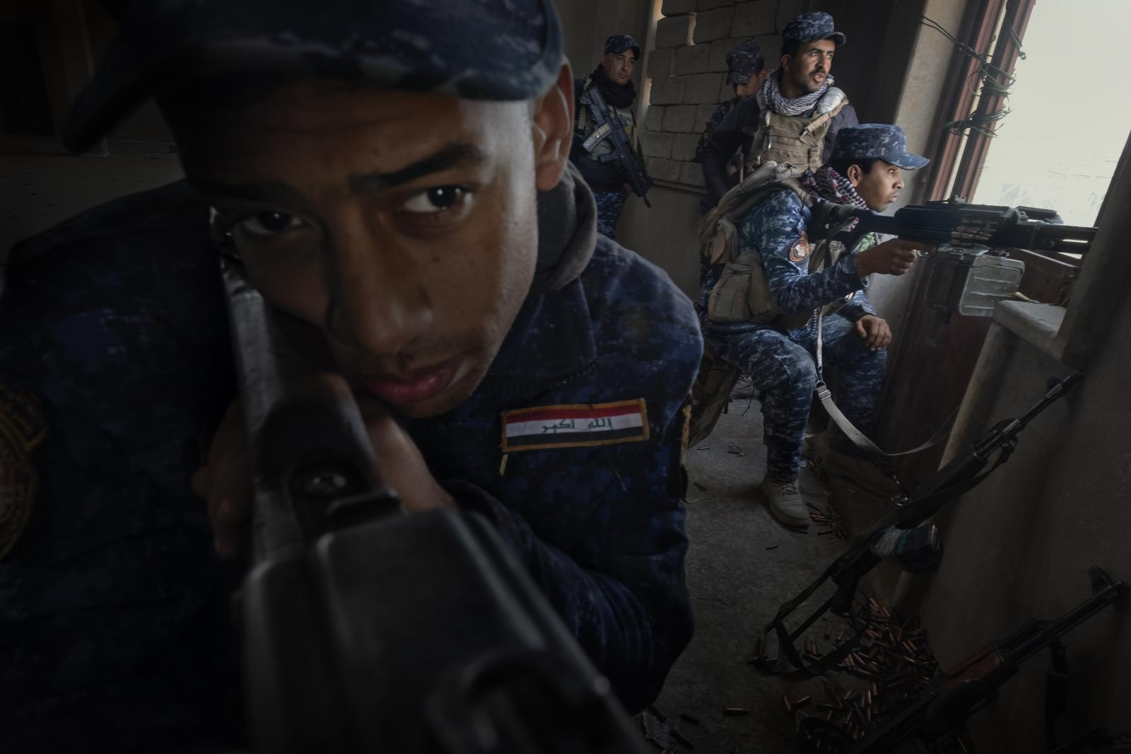 Federal Police soldiers (elite units of the Iraqi Security Forces) on the front lines near the airport in Mosul remain alert as they await another imminent ISIS attack. The large number of spent shells (lower right margin) is a sign of the ferocity of the fighting that takes place every day (Iraq, 2017)