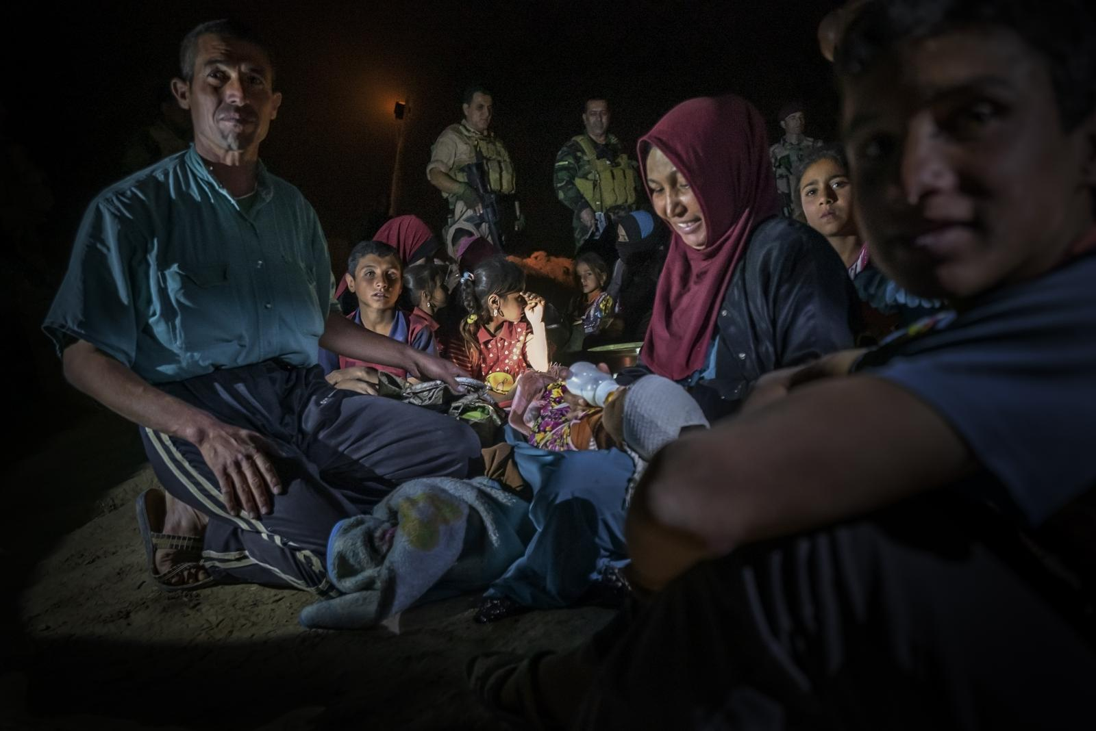 Refugees, who had fled desperately from the city of Mosul during the night, risking death if ISIS captured them, were rescued by Kurdish Peshmerga soldiers (those who face death) in Al-Qubeiba and later transferred to a refugee camp (Iraq, 2016)