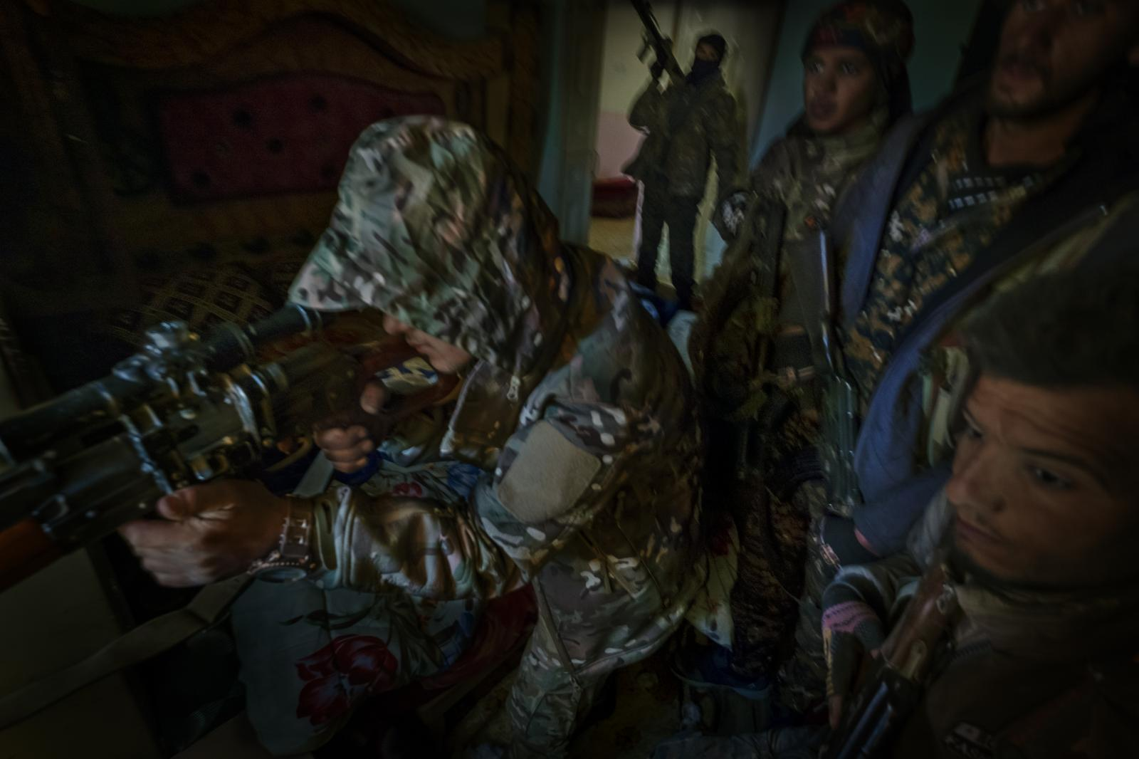 Members of the Syrian Democratic Forces (SDF) with a sniper, in a position in a house on the front lines in Deir ez-Zor, during the last battle and the final collapse of the ISIS caliphate. The SDF were created in October 2015, and are a military alliance of Kurdish, Arab, Assyrian, Armenian, Turkmen and Circassian militias (Syria, 2019)