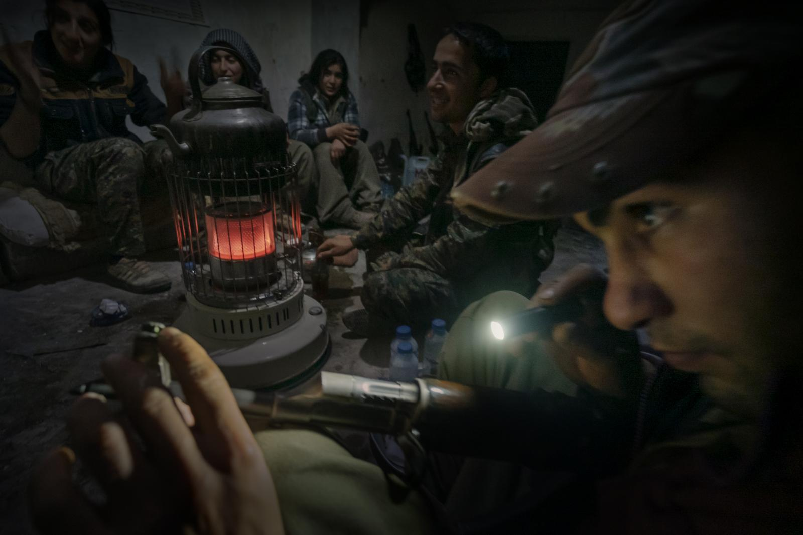 Members of the Kurdistan Workers' Party (PKK), Free Women's Units, Kurdistan Workers' Party (YJA STAR) and the Marxist-Leninist Communist Party of Turkey (MLKP) during the night, in a position a few yards away from ISIS fighters in the battle of Sinjar, from where they could distinctly hear the calls to morning prayers prior to the daily fighting (Iraq, 2015)