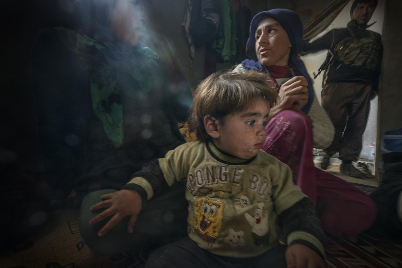 Zehra, a 25-year-old Kurdish woman who lost her 8-year-old daughter to a pulmonary infection in a refugee camp, sits with her other daughter in their home in the city of Kobane. Her husband, a People's Protection Units (YPG) fighter, is in the background. After four months of intense fighting, YPG, Women's Protection Units (YPJ), Peshmerga (those who face death) and Free Syrian Army (FSA) forces freed Kobane from the clutches of the ISIS caliphate (Syria, 2015)