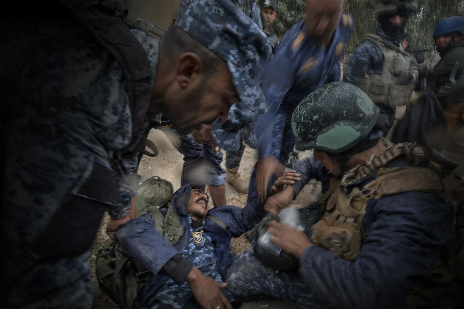 Comrades of a Federal Police soldier (elite units of the Iraqi Security Forces) injured in the explosion of an ISIS car bomb attend to him in the city of Mosul (Iraq, 2017)