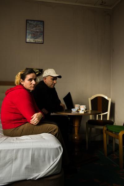 """Ekren (42jr.) agrarier en zijn vrouw Elmie Aliu uit Kosovo bivakeren sinds hun aankomst in Brussel in een door Fedasil betaalde hotelkamer. Het is er krap en bedompt maar dit hotel in een mooie buitenwijk van Brussel (Sint Pieters Woluwe) is beter dan menig andere asielzoeker. """"We krijgen elke dag twee checques van 6 euro, waarmee we eten etc. kunnen kopen. Jammer dat we geen buskaartjes kunnen aanschaffen, want 7 maanden in en rond dit hotel is wel lang. """"©Sanderdewilde.com"""