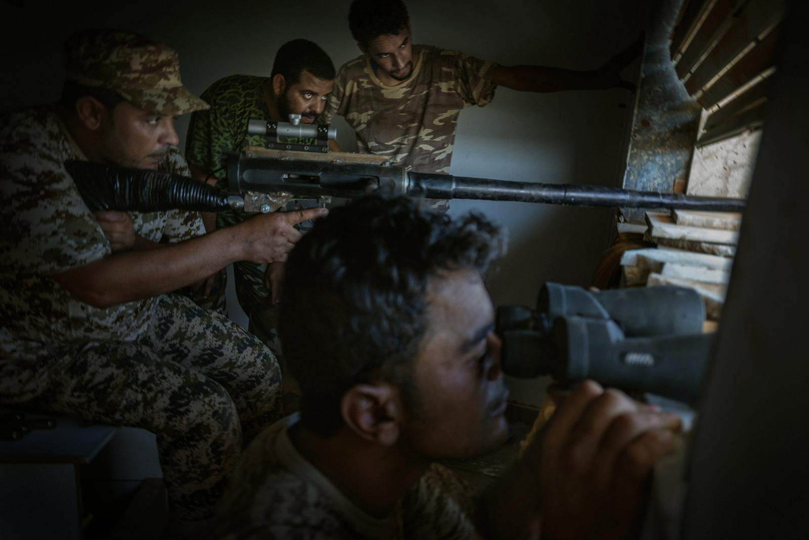 A sniper with a homemade rifle outfitted with a DShK machine gun barrel fires at ISIS positions in Sirte (2016).