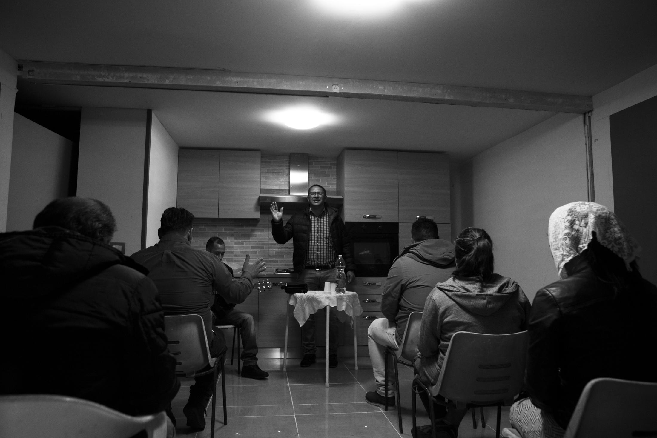 March 2017, nomad camp of Castelnuovo Rangone, Emilia Romagna, Italy. Prayer of the evangelical cult held inside a mobile home of the camp. Evangelical cults are gaining ground within the Sinti community. The shepherds, also of the Sinti ethnic group, move from field to field to support the various cults and involve an increasing number of faithful.