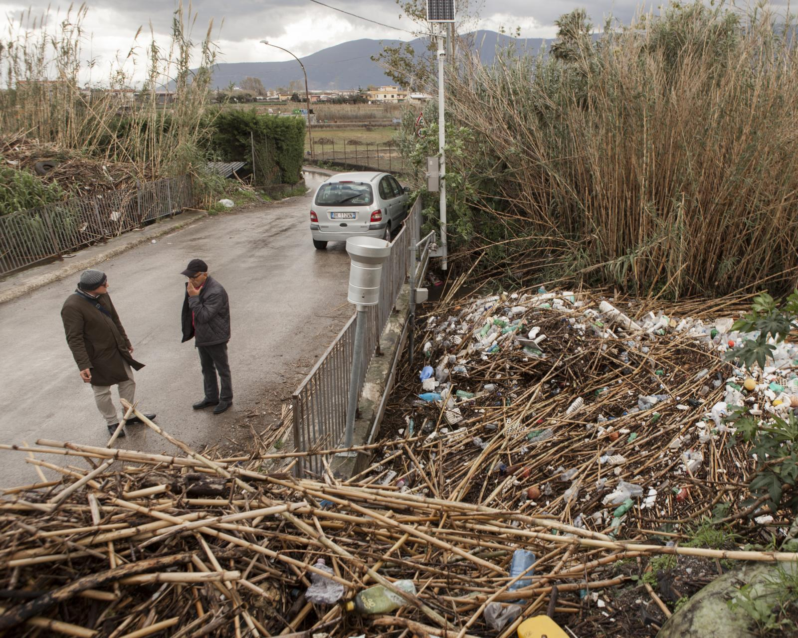 San Marzano Sul Sarno, Salerno, November 2018. Two men talk in front of the large block of solid waste brought from the canal. These rubbish, blocking along the course of the river, have raised the water level with consequent overflows during rainy or flooding days. The flooding often also involved the numerous cultivations present in the Sarno valley, leading to the contamination of vegetables with chemicals and waste spilled further upstream.