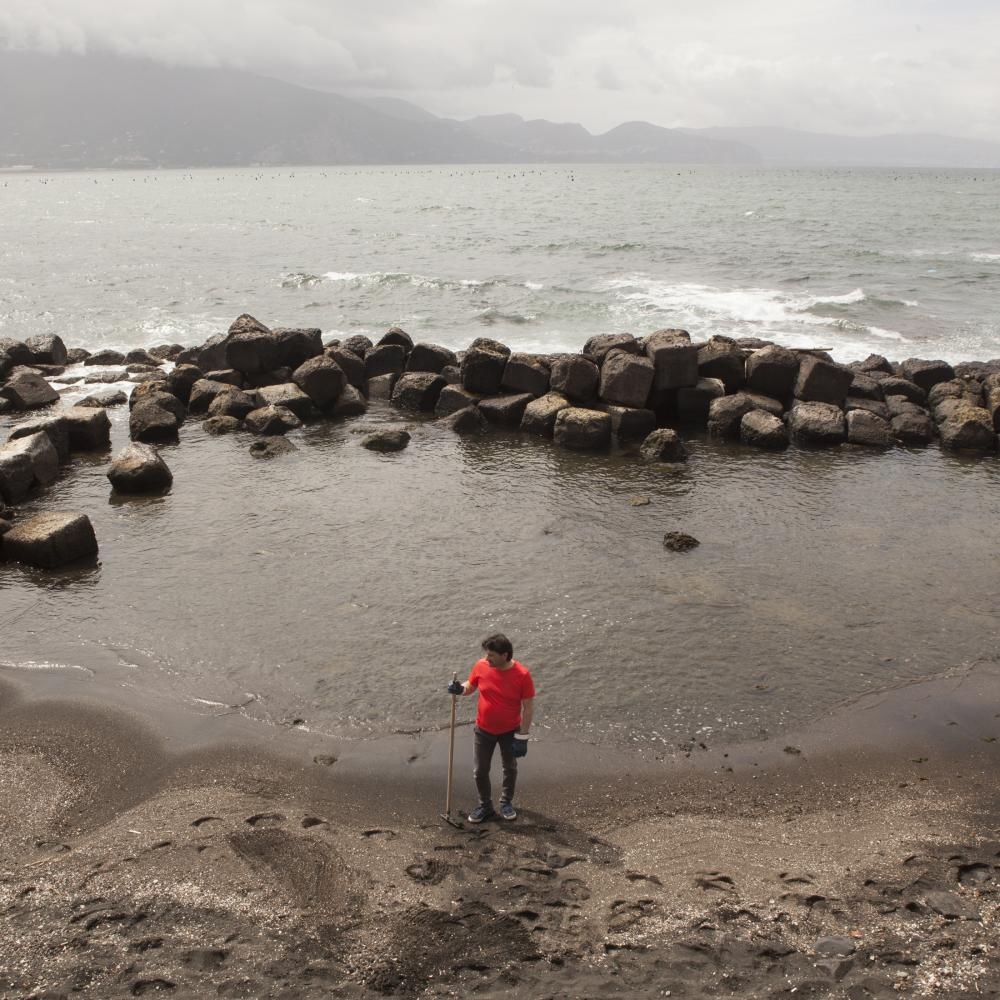 Torre Annunziata, April 2019. A volunteer rests once finished cleaning the beaches from waste sent back from the sea currents. This waste, chemical and solid waste, present in the river pours into the sea, making almost 10km of coast between the Gulf of Naples and the Amalfi Coast unsuitable for bathing.
