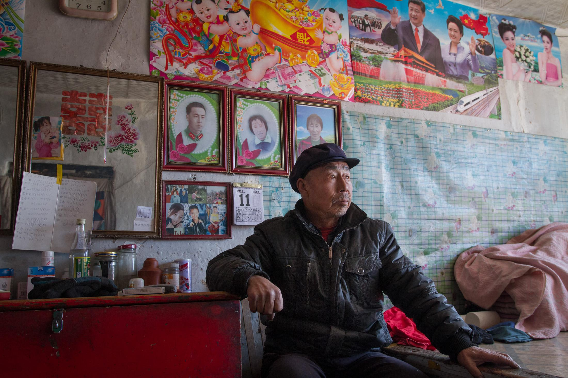 Taizicheng Villager Fan Youchang, 73, sits in his home posing for a picture in March 2016. He's lived in Taizicheng Village his whole life before having to move into Chongli downtown.