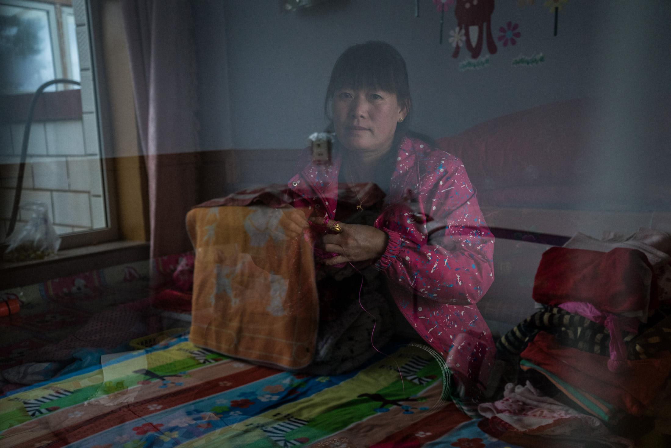 Hu Guihua sits in bed knitting at her home in Taizicheng village, Chongli, China, September 2015. The house has been demolished by the end of 2016. Hu is one of the villagers who later refuse to agree on the government's compensation, and take the case to court.