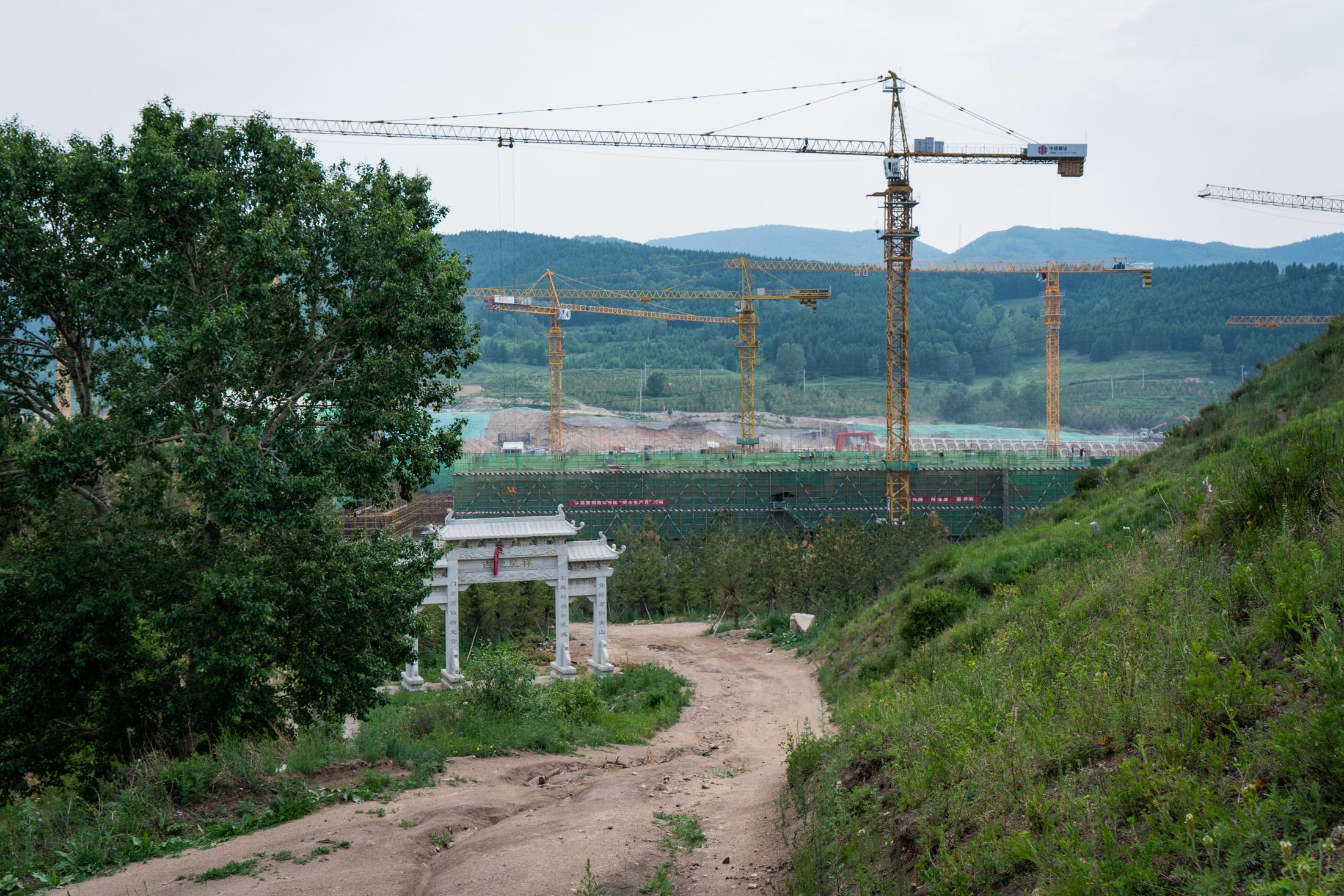 Taizicheng Ice and Snow Resort is under construction in the background, with a white archway for a cemetery seen in the foreground, June 2019.