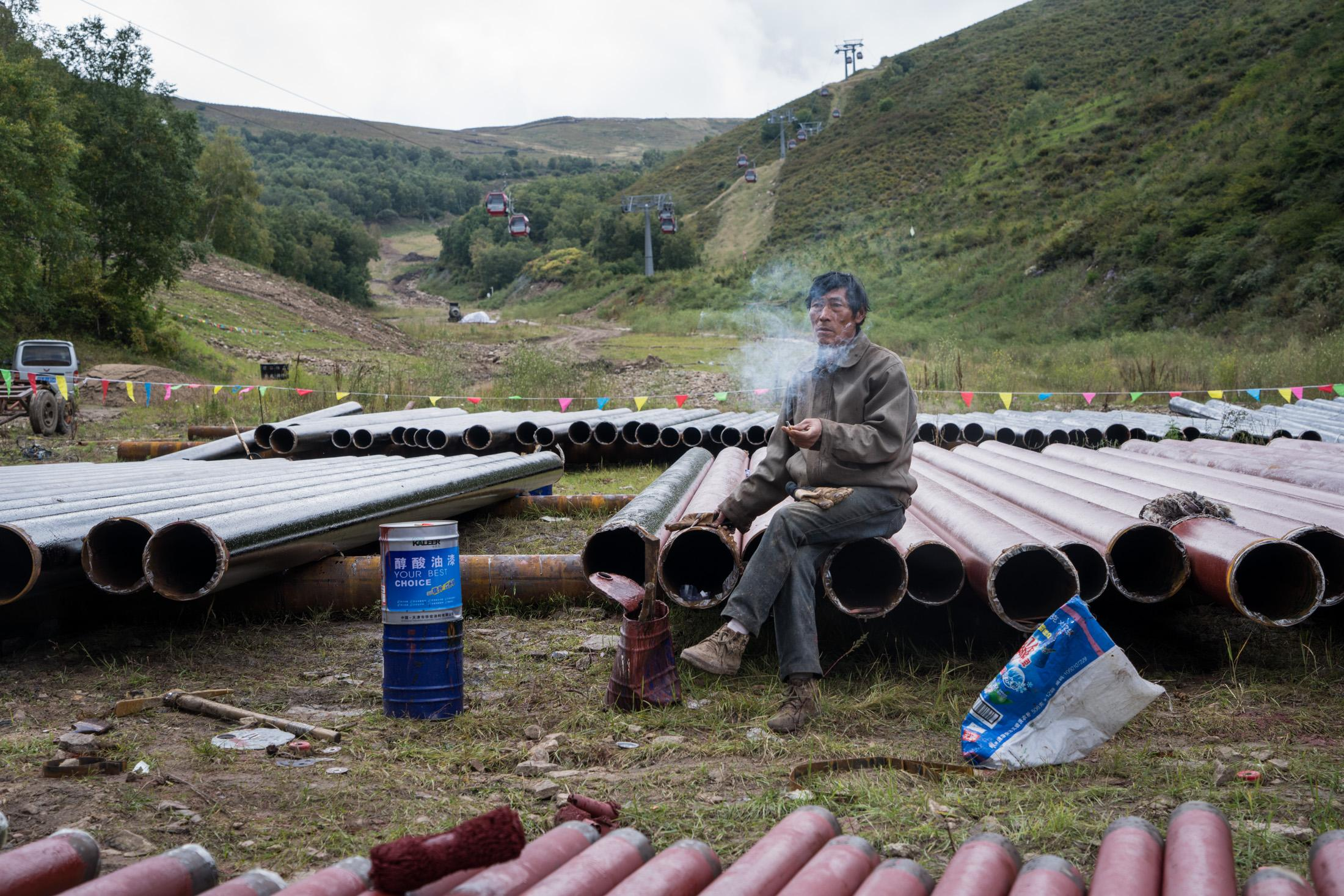 A worker takes a cigarette break at Genting Skiing Resort, Chongli, China in September 2015.