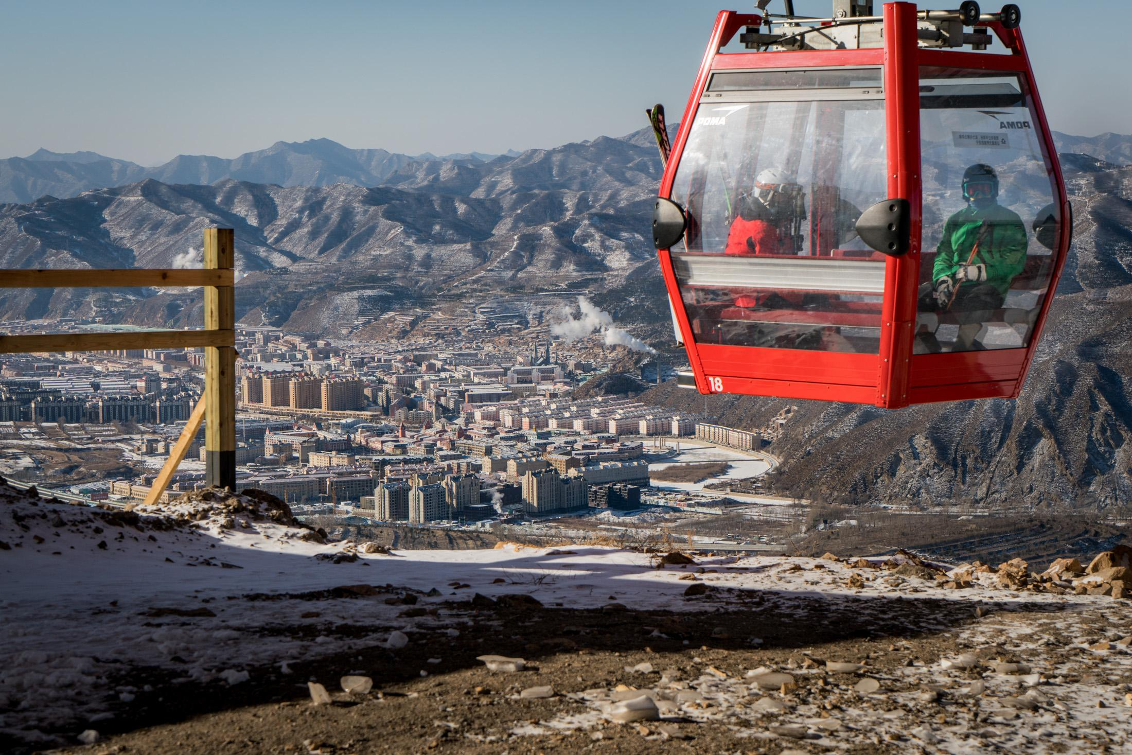 Skiers in a gondola arrive at the top of a slope at Galaxy Ski Resort in January, 2018. Chongli downtown, with all the newly built apartments, is seen in the background.