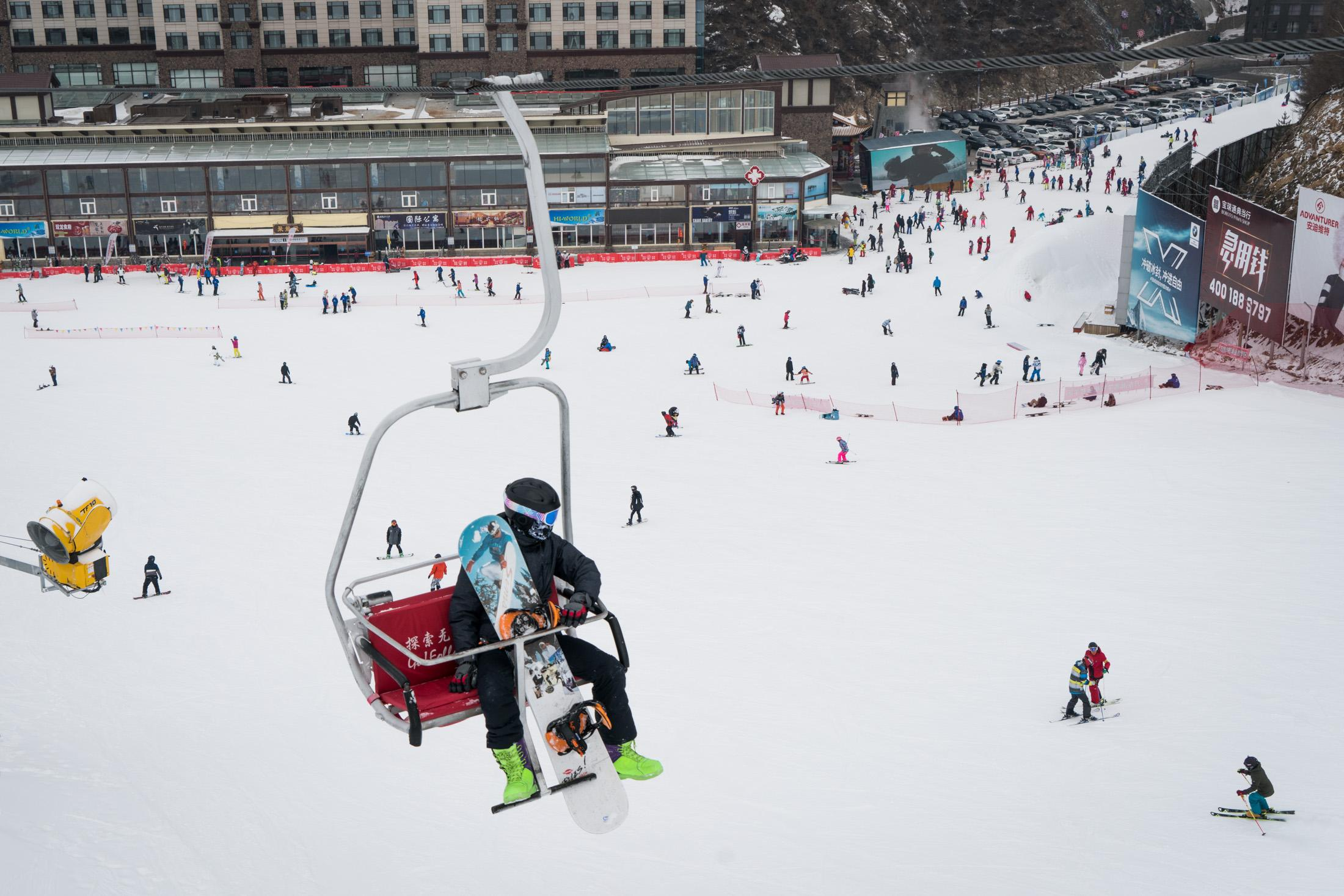 A snowboarder sits in a chairlift looking down at the slope in Wanlong Ski Resort in Chongli, China, January, 2018. Recreational ski and ski resorts started to develop in China around 2000. The number of ski resorts visits has increased dramatically in the past decade in China, from 5 million visits in 2008 to 19.7 million visits in 2018, according to China Ski Industry White Book published last year.