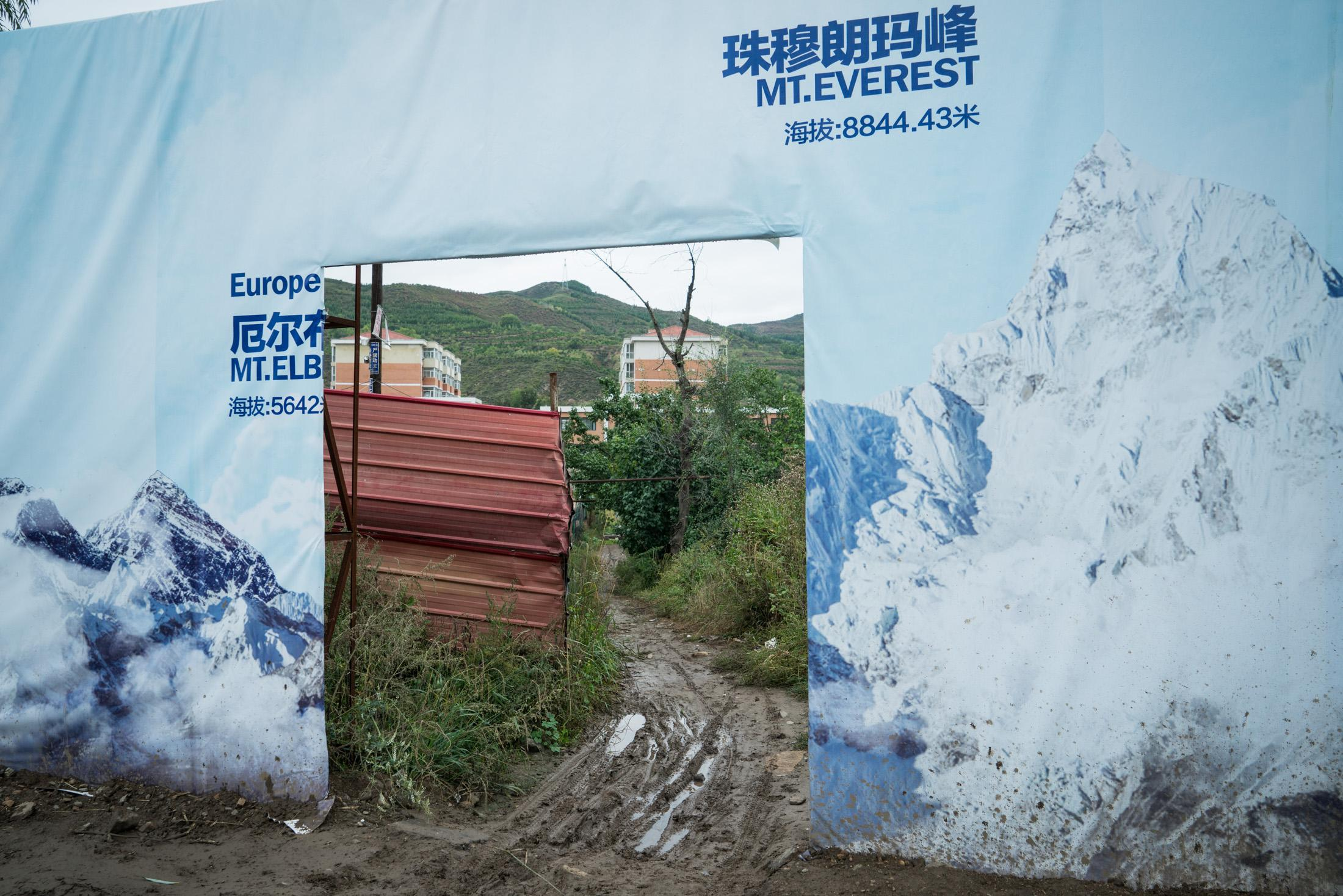 An advertisement board covered by pictures of the world's highest mountains in Chongli, China, in September 2015.