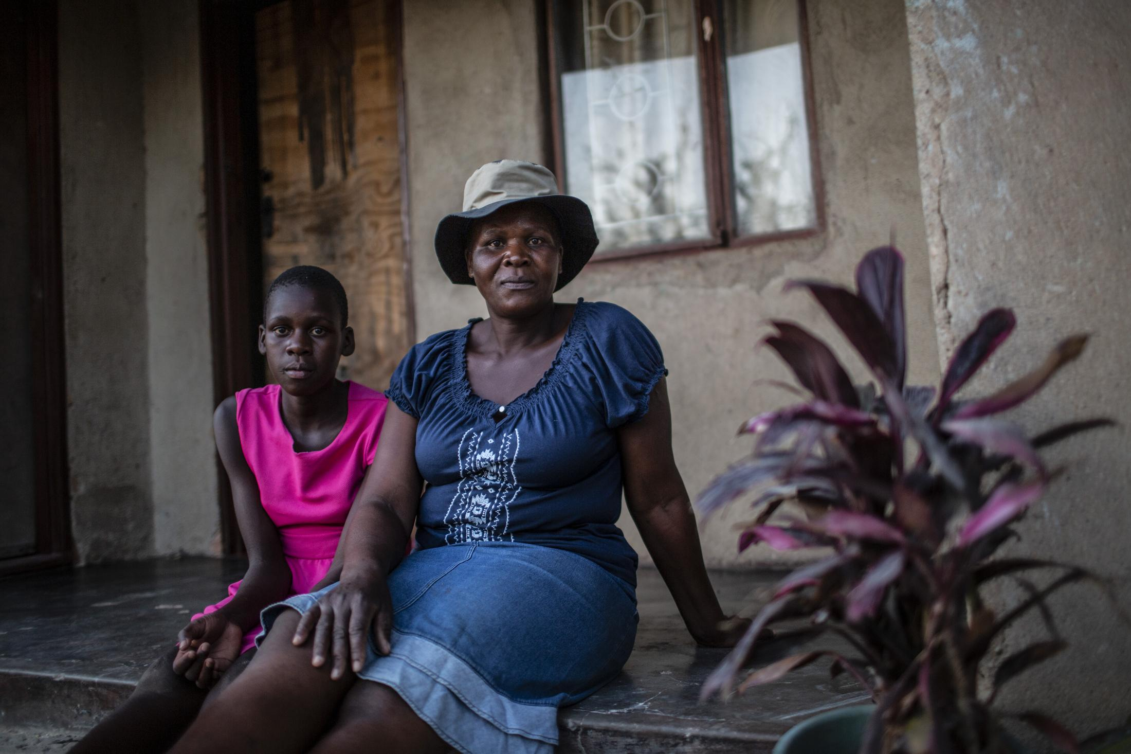 Tariro Chinamo (43) (R) and her daughter Lana Fariva (14) are pictured at their home which is 7kms away from the R4 Rural Resilience Project in Masvingo, Zimbabwe on October 07, 2019. The family has no electricity or water at home and have to walk for over a km to a spring to fetch water everyday. They have no choice but to use this for drinking and cooking as well, so it will be boiled. The project has benefitted them greatly, providing fresh fish and vegetables for the family. Tariro has also gained a lot of knowledge about farming and financial literacy and is able to implement these strategies in other aspects of her life. She has now started her own poultry and goat farming initiative.