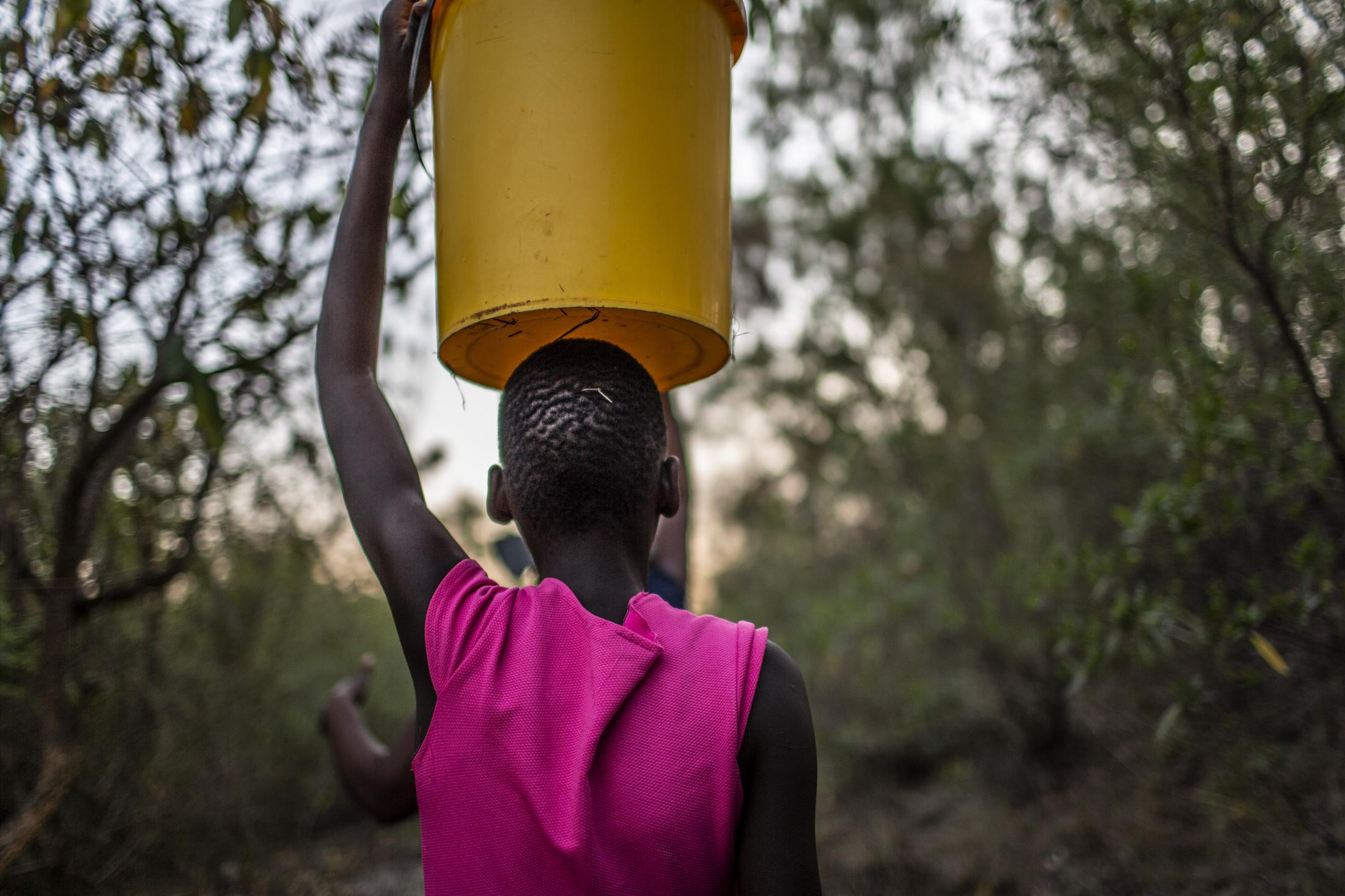 Lana Fariva (14) walks to fetch water in Masvingo, Zimbabwe on October 07, 2019. The family has no electricity or water at home and have to walk for over a km to a spring to fetch water everyday. They have no choice but to use this for drinking and cooking as well, so it will be boiled.