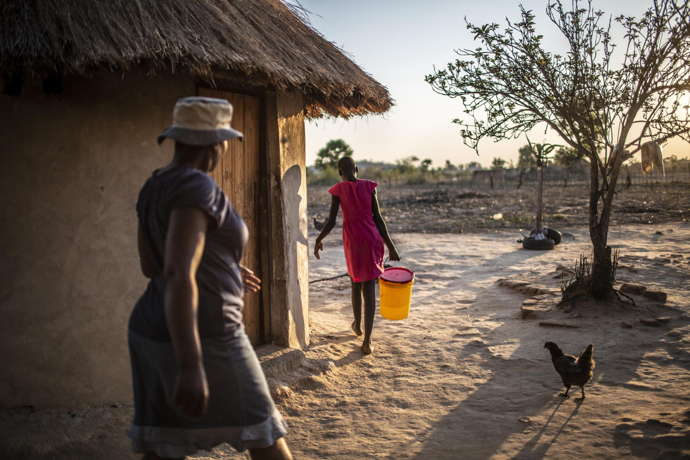 Tariro Chinamo (43) (L), pictured at her home which is 7kms away from the R4 Rural Resilience Project, prepares to go fetch water with her daughter Lana Fariva (14) in Masvingo, Zimbabwe on October 07, 2019. The family has no electricity or water at home and have to walk for over a km to a spring to fetch water everyday. They have no choice but to use this for drinking and cooking as well, so it will be boiled.