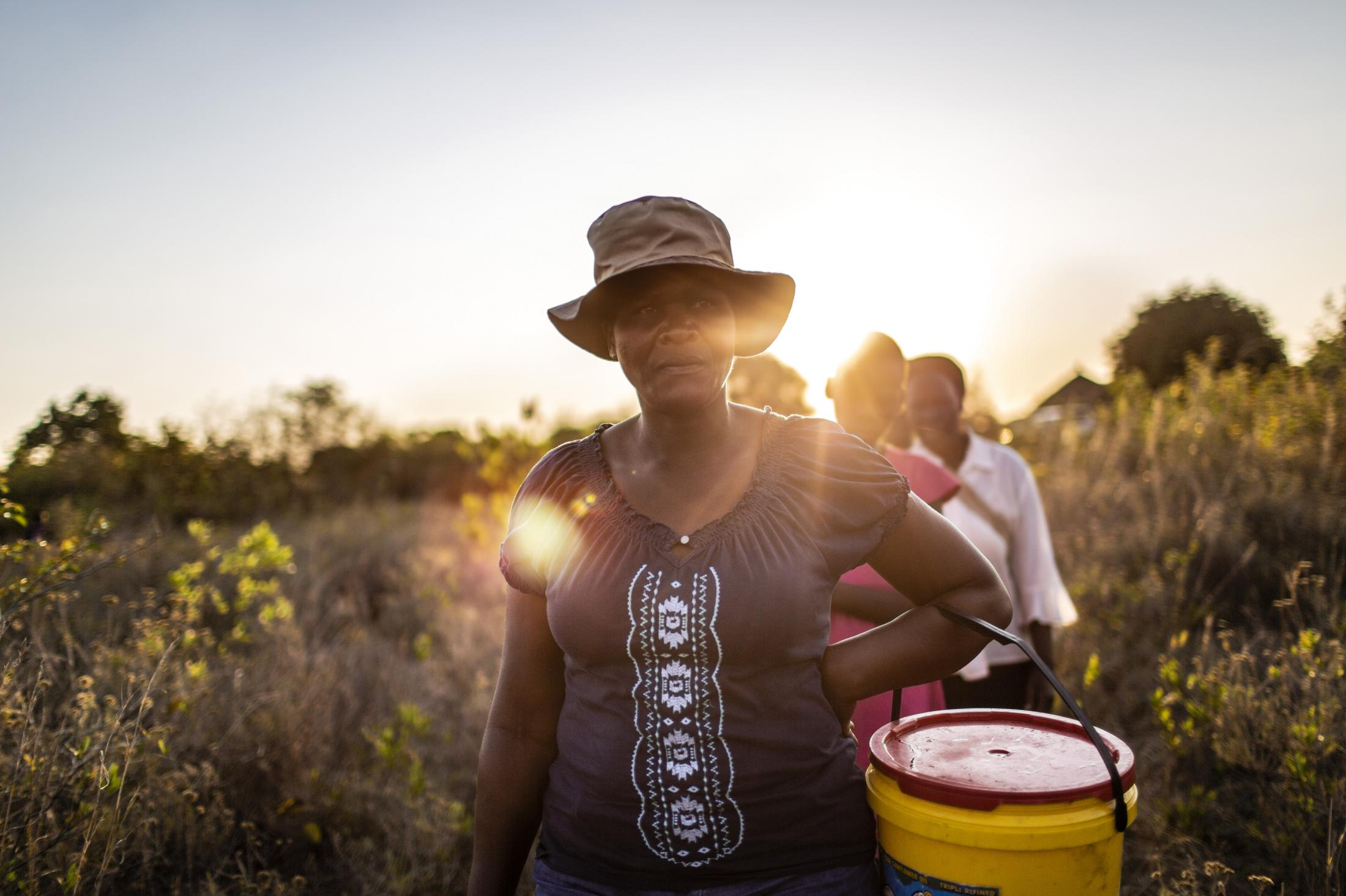 Tariro Chinamo (43) (L), walks with her daughter, Lana Fariva (14) and her mother-in-law Christina Chamissa (58) to fetch water in Masvingo, Zimbabwe on October 07, 2019. The family has no electricity or water at home and have to walk for over a km to a spring to fetch water everyday. They have no choice but to use this for drinking and cooking as well, so it will be boiled.
