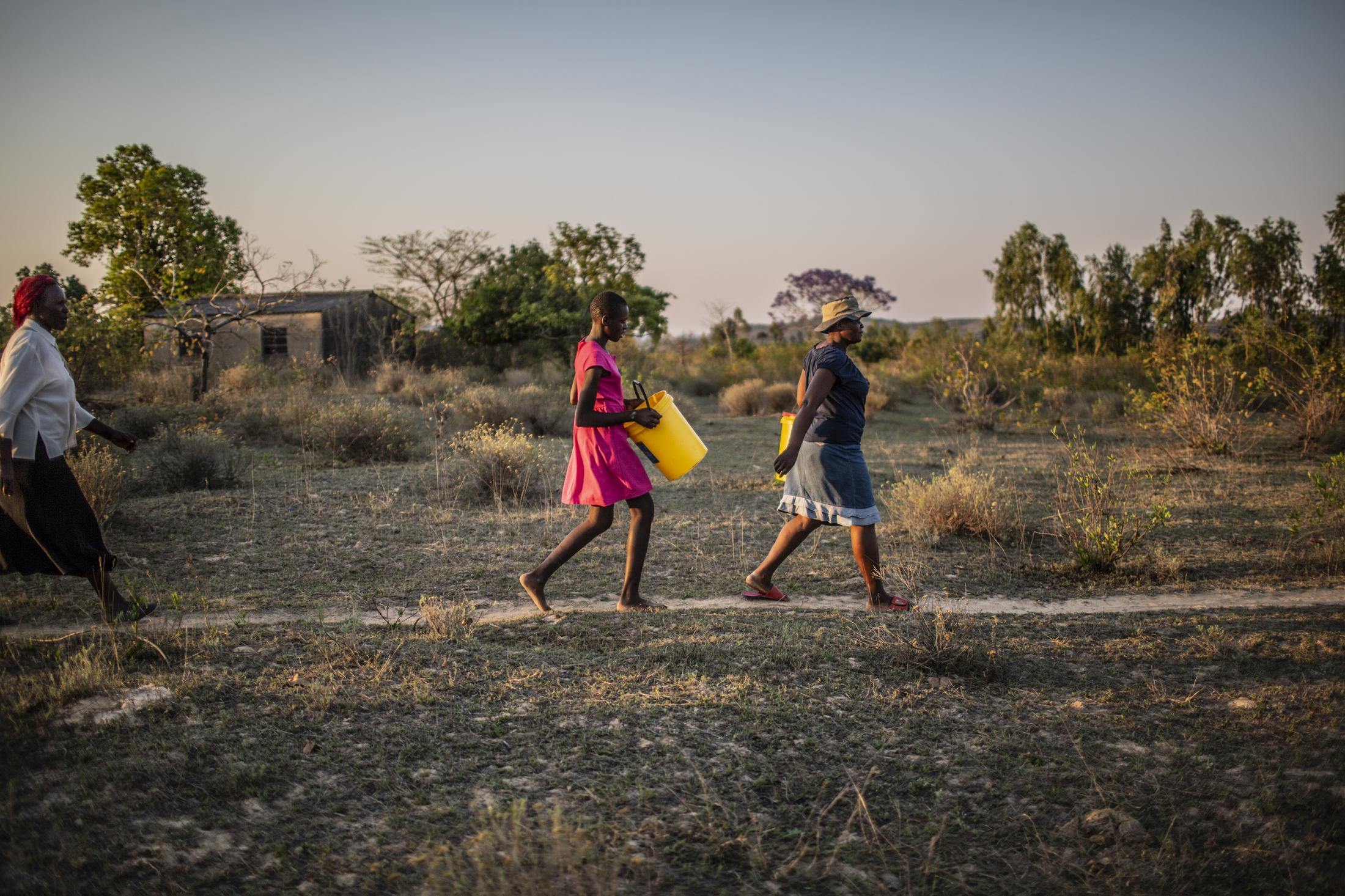 Tariro Chinamo (43) (R), walks with her daughter, Lana Fariva (14) and her mother-in-law Christina Chamissa (58) to fetch water in Masvingo, Zimbabwe on October 07, 2019. The family has no electricity or water at home and have to walk for over a km to a spring to fetch water everyday. They have no choice but to use this for drinking and cooking as well, so it will be boiled.