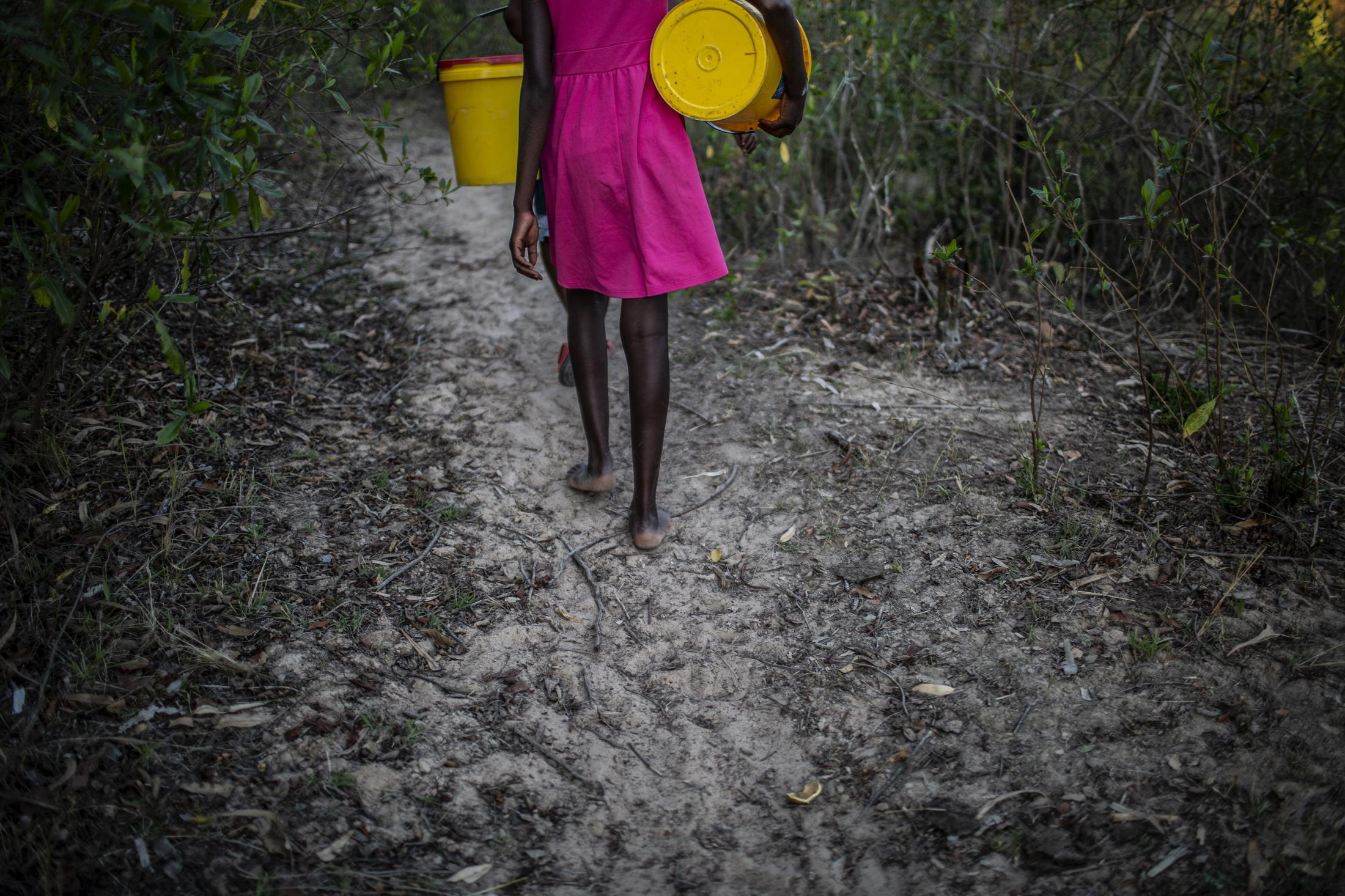 Lana Fariva (14) walks to a nearby spring to fetch water in Masvingo, Zimbabwe on October 07, 2019. The family has no electricity or water at home and have to walk for over a kilometre to fetch water everyday. They have no other option but to use this for drinking and cooking as well. Gulshan Khan for the Swiss Agency for Development and Cooperation (SDC)