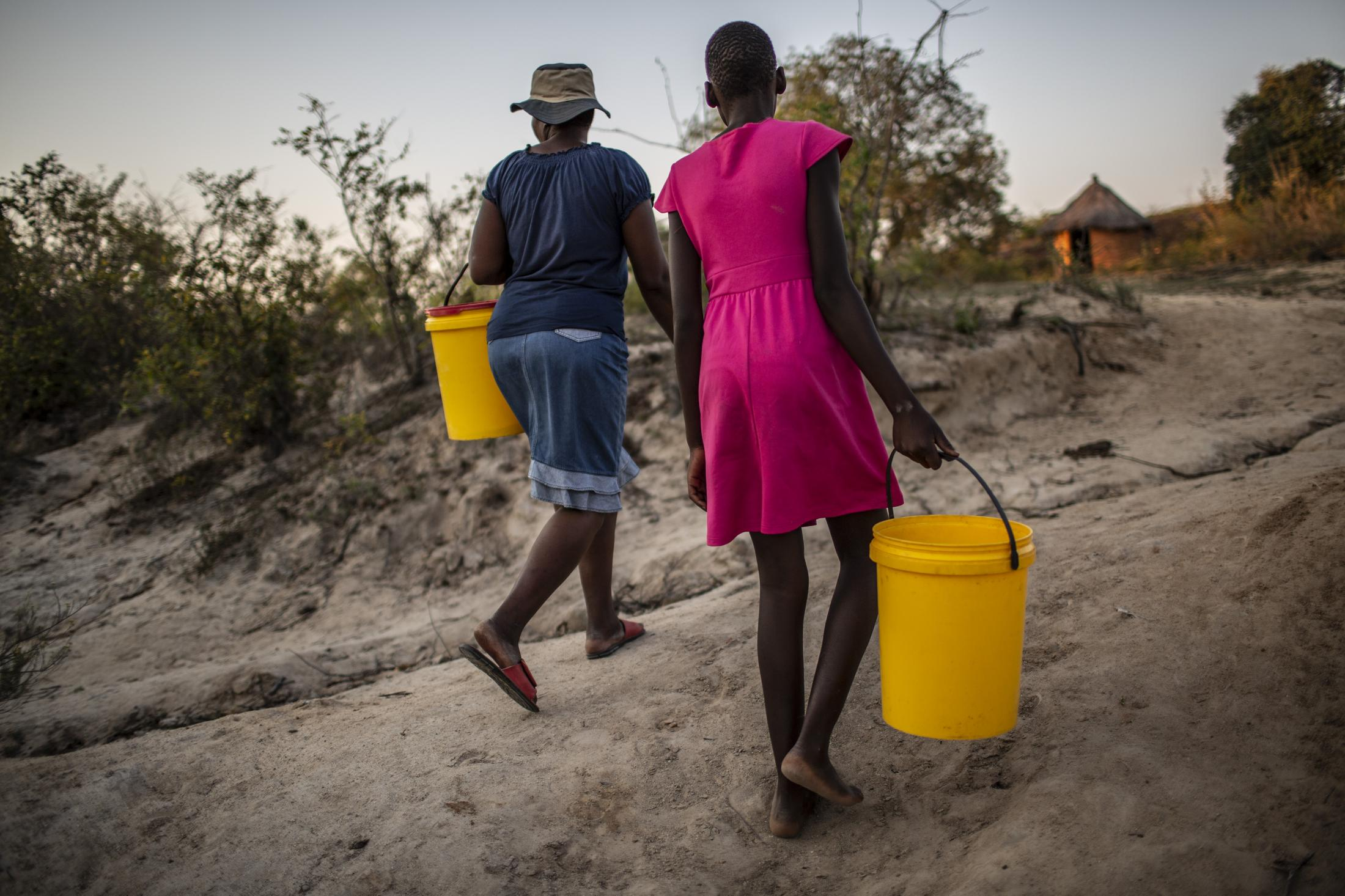 Tariro Chinamo (43) (R), walks with her daughter, Lana Fariva (14) to fetch water in Masvingo, Zimbabwe on October 07, 2019. The family has no electricity or water at home and have to walk for over a km to a spring to fetch water everyday. They have no choice but to use this for drinking and cooking as well, so it will be boiled.