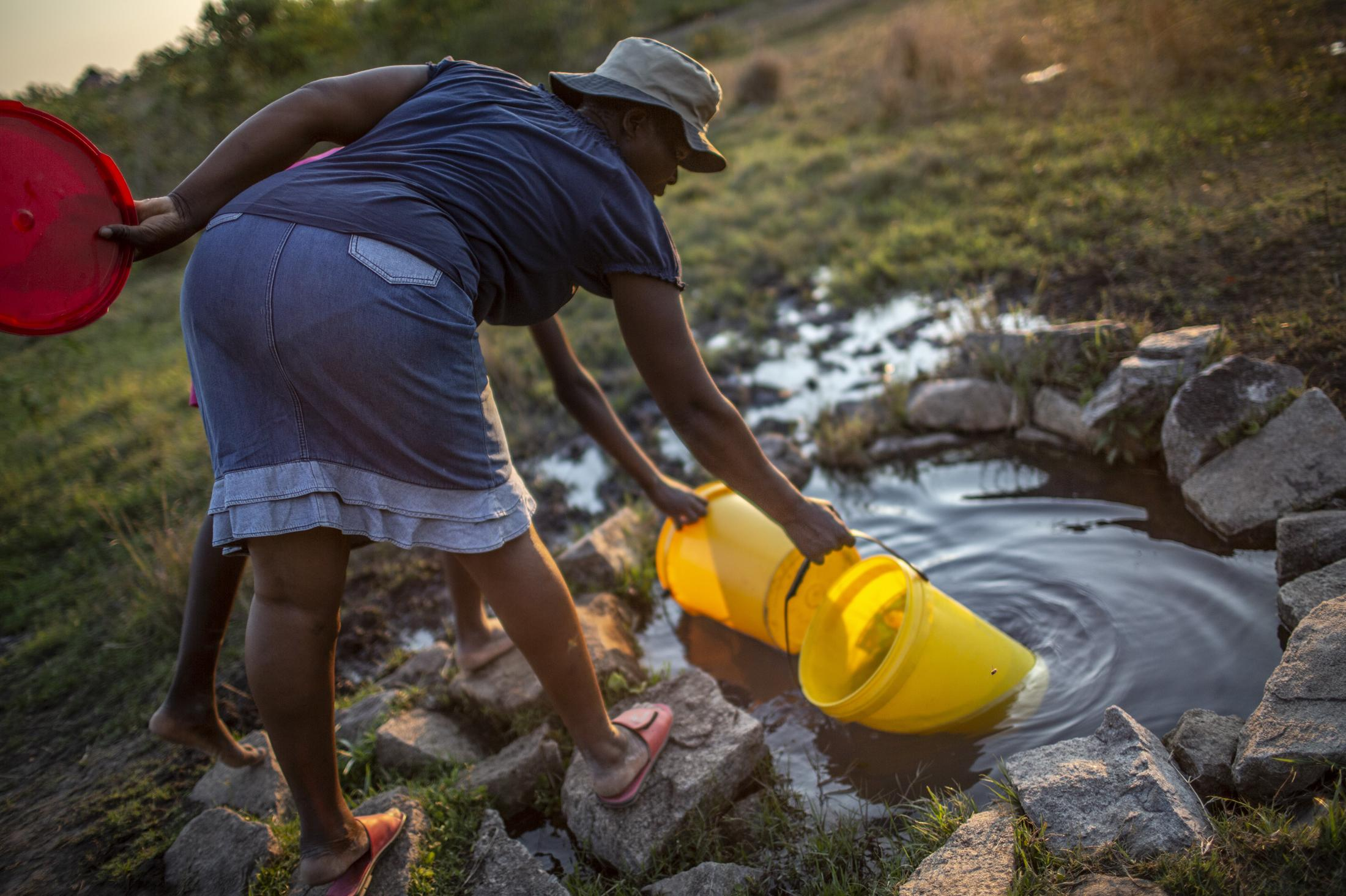 Tariro Chinamo (43) (foreground) and her daughter, Lana Fariva (14) fill their buckets in a spring in Masvingo, Zimbabwe on October 07, 2019. The family has no electricity or water at home and have to walk for over a km to a spring to fetch water everyday. They have no choice but to use this for drinking and cooking as well, so it will be boiled.