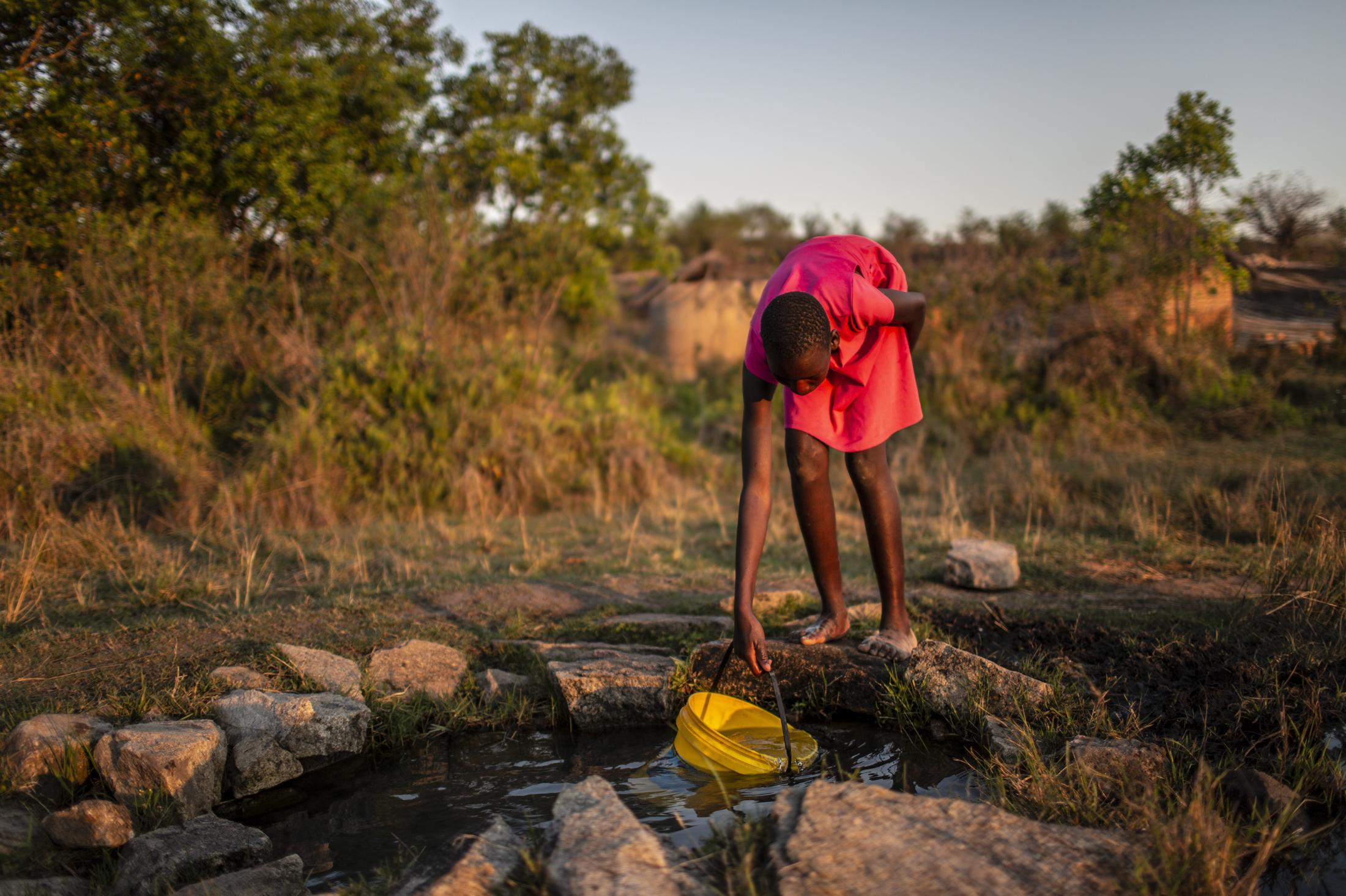 Lana Fariva (14) fills her bucket with water from a spring in Masvingo, Zimbabwe on October 07, 2019. The family has no electricity or water at home and have to walk for over a km to a spring to fetch water everyday. They have no choice but to use this for drinking and cooking as well, so it will be boiled.
