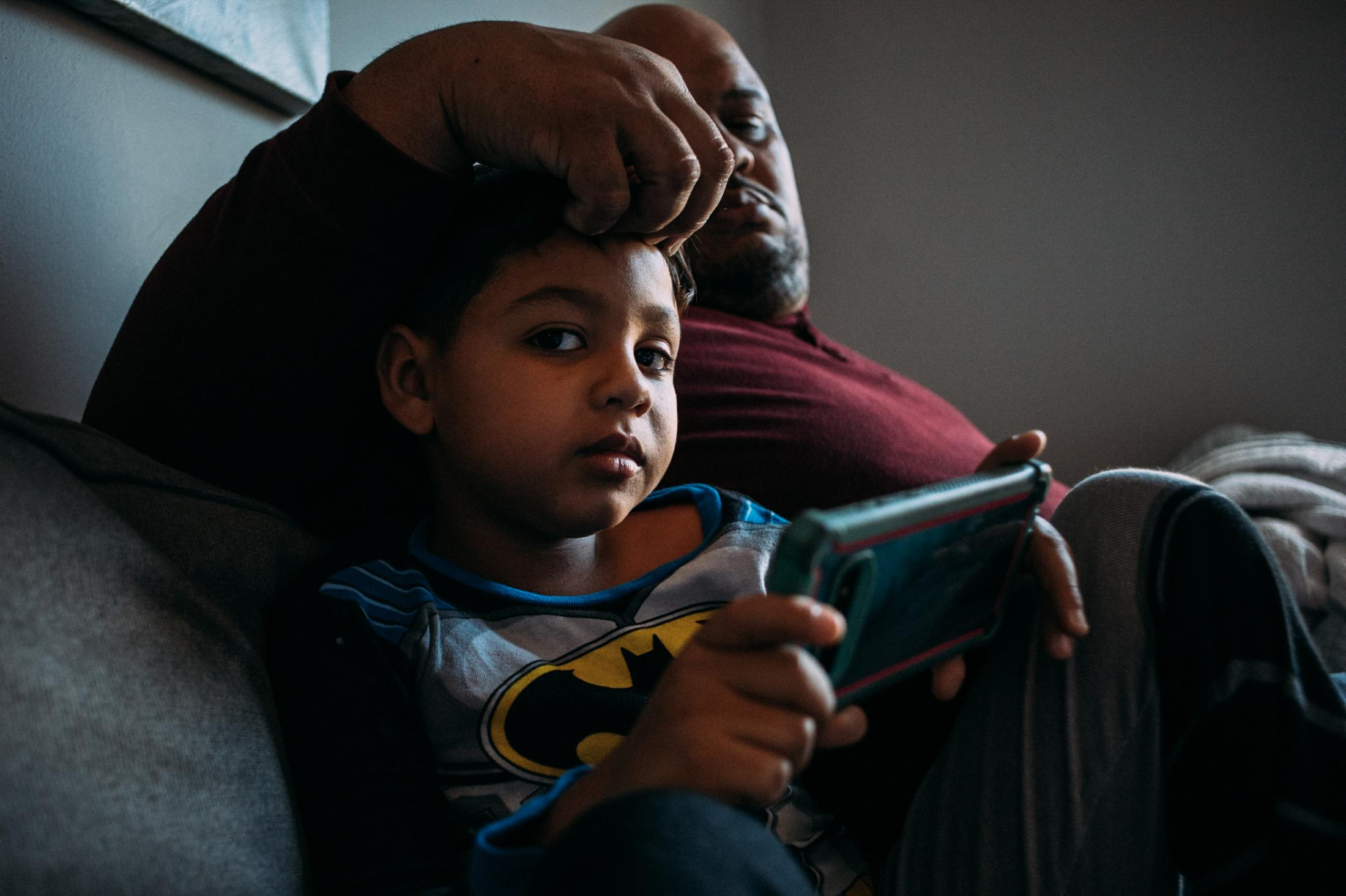 Alejandro Quiles Garcia, 40, middle, and his son, Alexander Quiles Cortés, 7, sit at a relative's home in Manhattan, New York and take advantage of a rare morning uninterrupted by the ongoing earthquakes at their hometown in Puerto Rico, for CNN