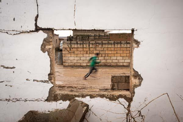 A view throught destroyed window of a child playing in the streets of Tel Nasri near the frontline against yihadists and Turkish Army. After the withdrawal of US troops from northern Syria in October 2019, Turkey launched an offensive against the predominantly Kurdish areas in the northeast of the country along Islamist forces. Calls for war crimes investigations into the conduct of Ankara-backed militias are mounting ever since. (Andoni Lubaki / Euskal Fondoa)
