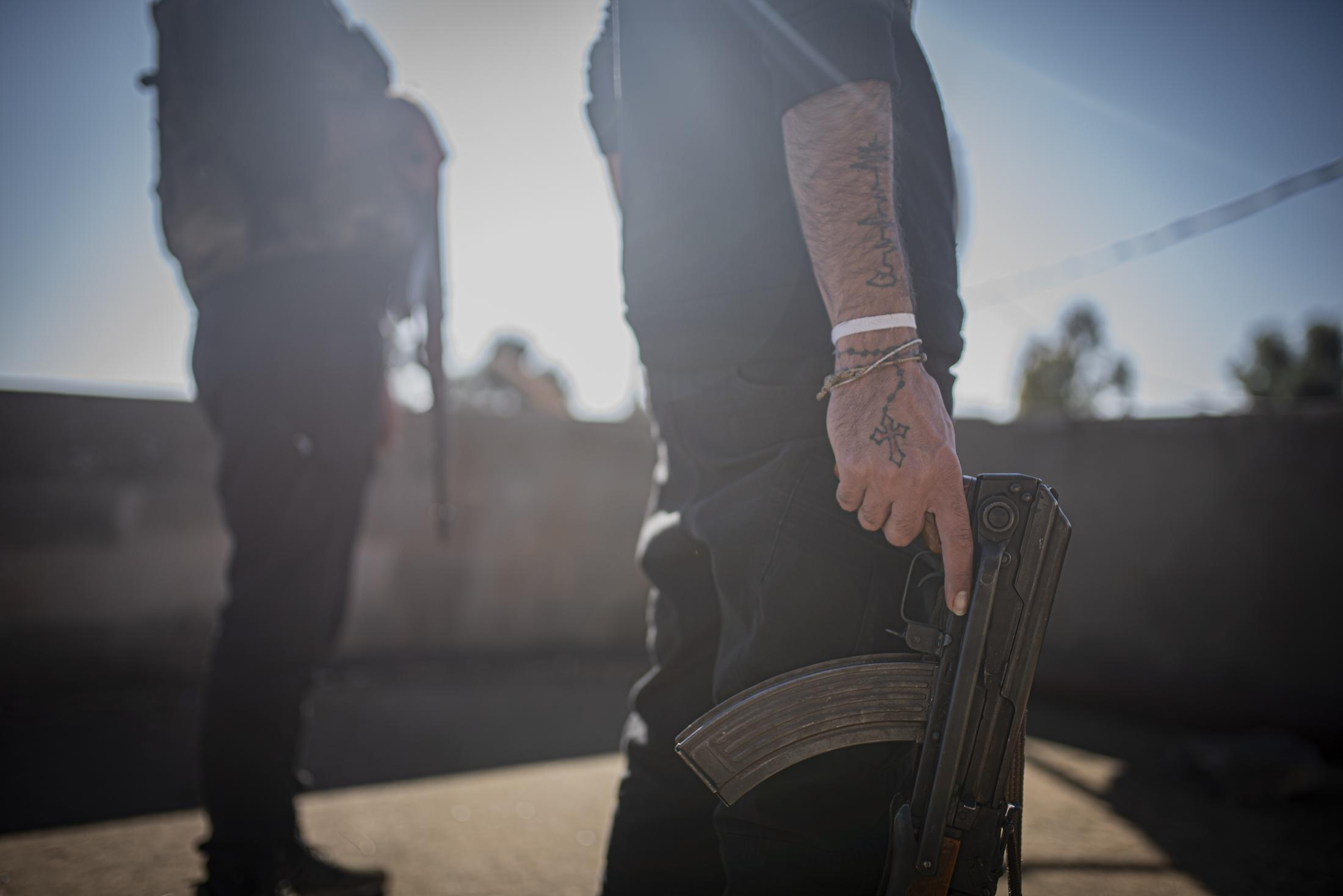 A christian militia soldier hanging a Kalashnikov and showin the christian cross tatoo in his hand in the frontline of Tel Nasri. After the withdrawal of US troops from northern Syria in October 2019, Turkey launched an offensive against the predominantly Kurdish areas in the northeast of the country along Islamist forces. Calls for war crimes investigations into the conduct of Ankara-backed militias are mounting ever since. (Andoni Lubaki / Euskal Fondoa)