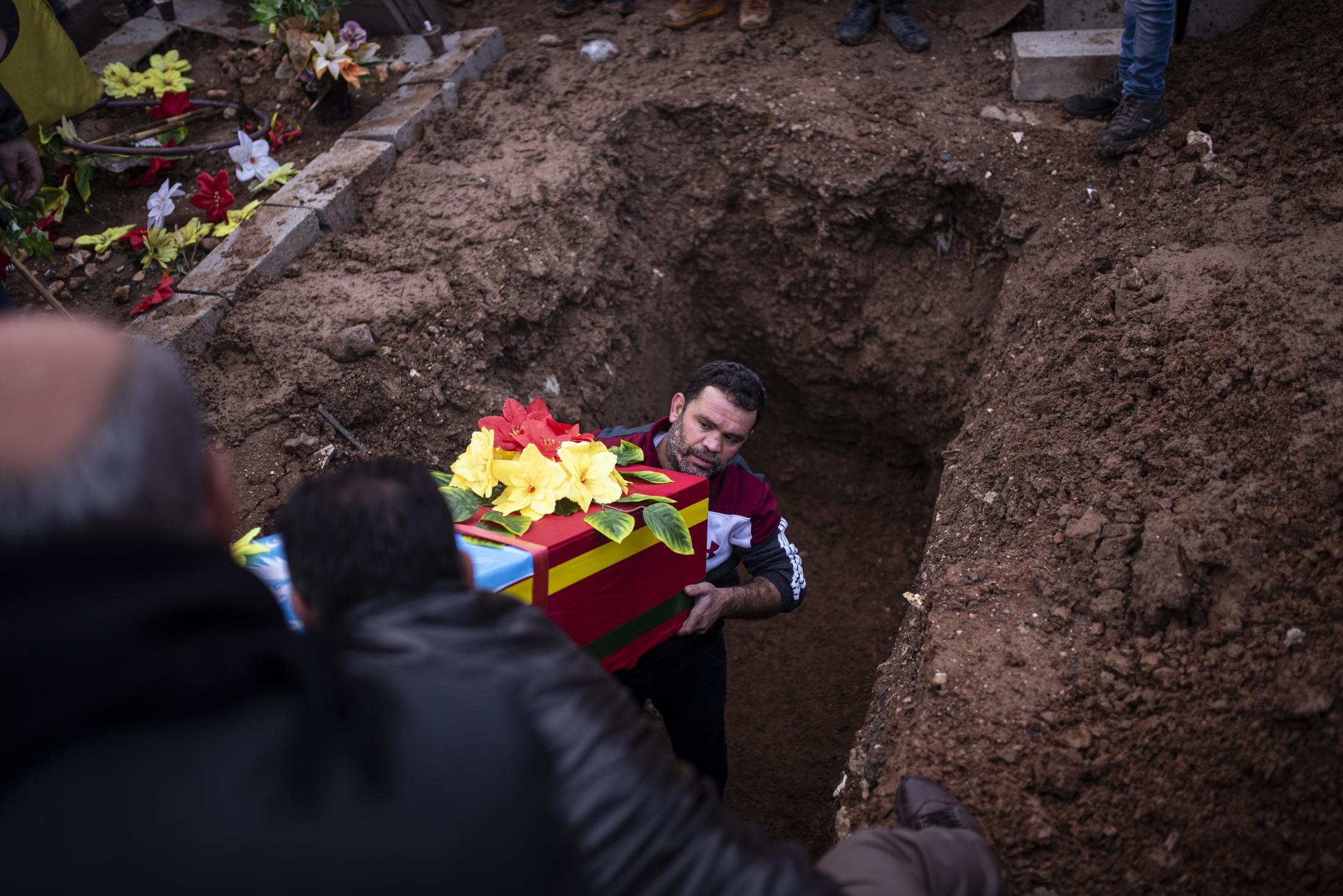 Comrades help in the burial of a Asayis killed in a mortar attack in the Tel Tamer area. After the withdrawal of US troops from northern Syria in October 2019, Turkey launched an offensive against the predominantly Kurdish areas in the northeast of the country along Islamist forces. Calls for war crimes investigations into the conduct of Ankara-backed militias are mounting ever since. (Andoni Lubaki / Euskal Fondoa)
