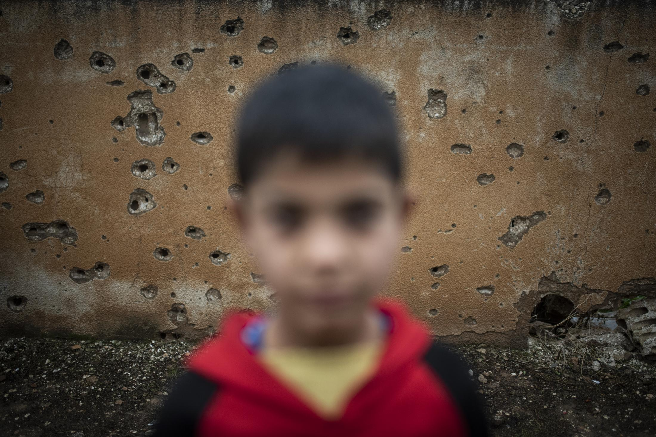A portrait of a boy in front of a holed by bullets wall in Tel Nasri, near the frontline against yihadists and Turkish Army. After the withdrawal of US troops from northern Syria in October 2019, Turkey launched an offensive against the predominantly Kurdish areas in the northeast of the country along Islamist forces. Calls for war crimes investigations into the conduct of Ankara-backed militias are mounting ever since. (Andoni Lubaki / Euskal Fondoa)