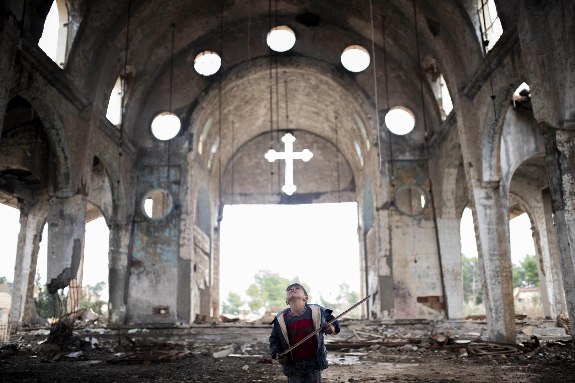 Child playing war games inside a destroyed church by ISIS in Tel Nasri town, near the frontline in the war against yihadist and Turkey. After the withdrawal of US troops from northern Syria in October 2019, Turkey launched an offensive against the predominantly Kurdish areas in the northeast of the country along Islamist forces. Calls for war crimes investigations into the conduct of Ankara-backed militias are mounting ever since. (Andoni Lubaki / Euskal Fondoa)