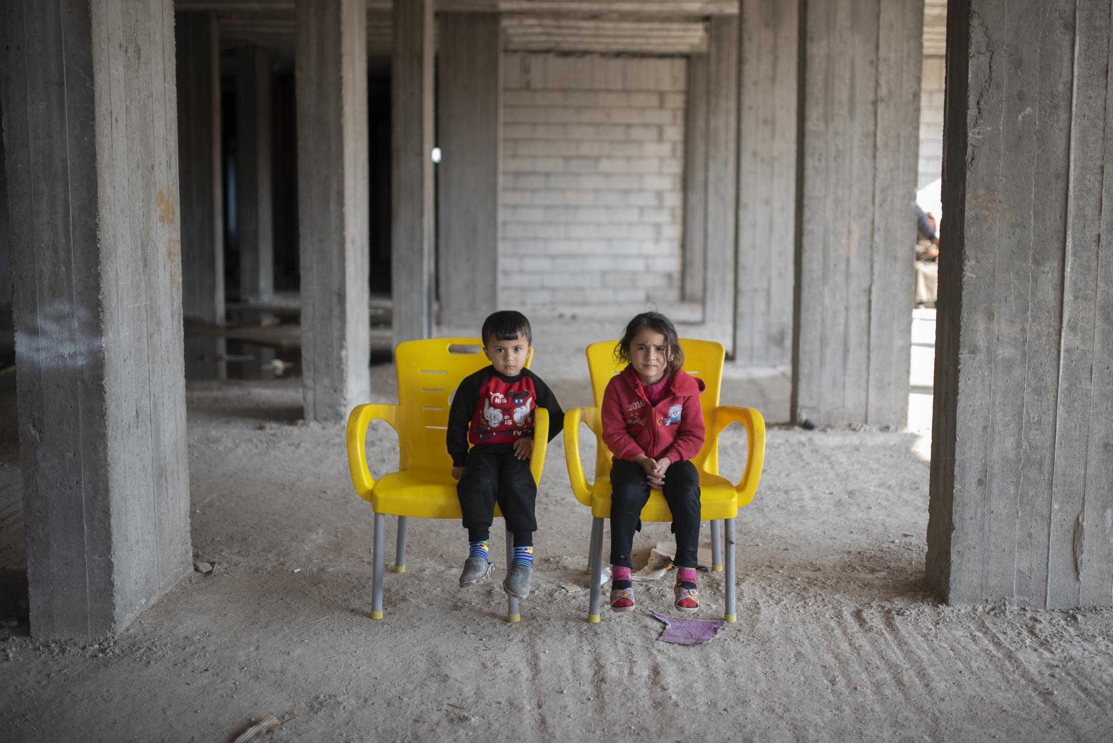 A boy and a girl waiting their father in yellow chairs inside a building in construction. After the withdrawal of US troops from northern Syria in October 2019, Turkey launched an offensive against the predominantly Kurdish areas in the northeast of the country along Islamist forces. Calls for war crimes investigations into the conduct of Ankara-backed militias are mounting ever since. (Andoni Lubaki / Euskal Fondoa)