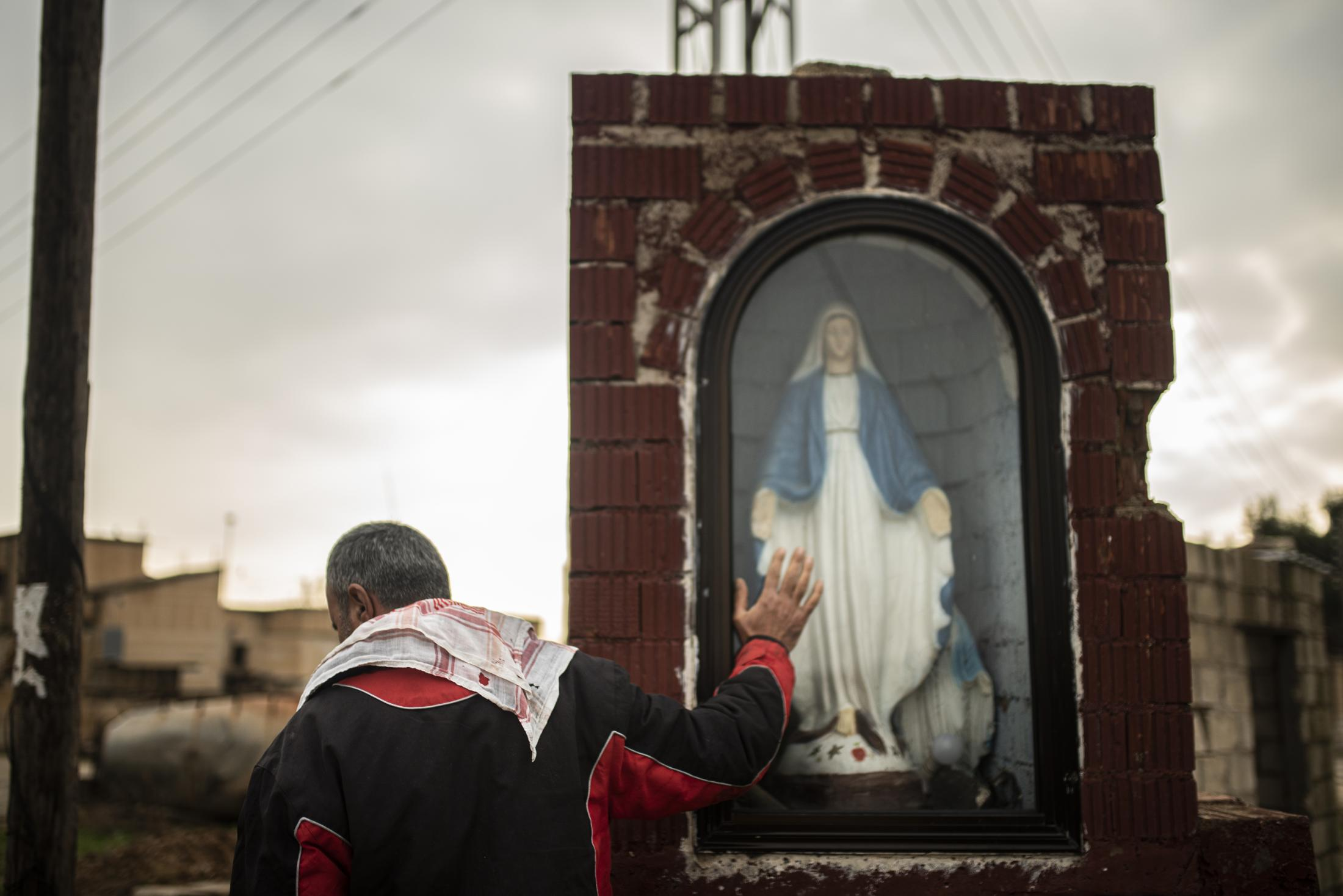 A christian inhabitant of Tel Nasri touching the figure of Mother Mary in the entry of the town few kilometers far away from the frontline against yihadists and Turkish Army. After the withdrawal of US troops from northern Syria in October 2019, Turkey launched an offensive against the predominantly Kurdish areas in the northeast of the country along Islamist forces. Calls for war crimes investigations into the conduct of Ankara-backed militias are mounting ever since. (Andoni Lubaki / Euskal Fondoa)