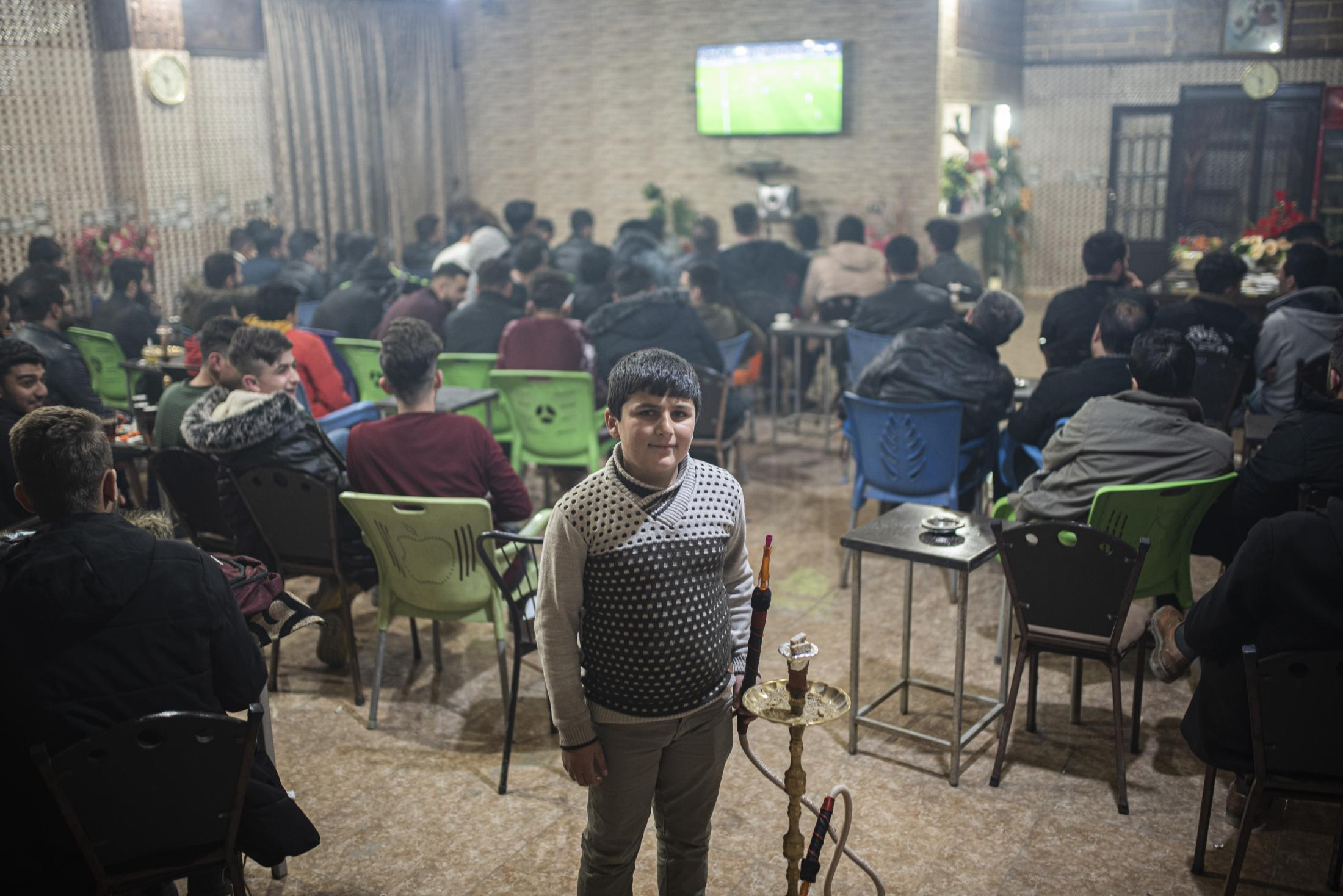 Ahmed, a Serekaniye refugee, working in a Sisha Bar during the clasico match (Barcelona - Madrid). Ahmed lost his father when yihadists kill him publicy in the streets of his home town Serekaniye and now is working in his cousin bar in Qamishlo. After the withdrawal of US troops from northern Syria in October 2019, Turkey launched an offensive against the predominantly Kurdish areas in the northeast of the country along Islamist forces. Calls for war crimes investigations into the conduct of Ankara-backed militias are mounting ever since. (Andoni Lubaki / Euskal Fondoa)