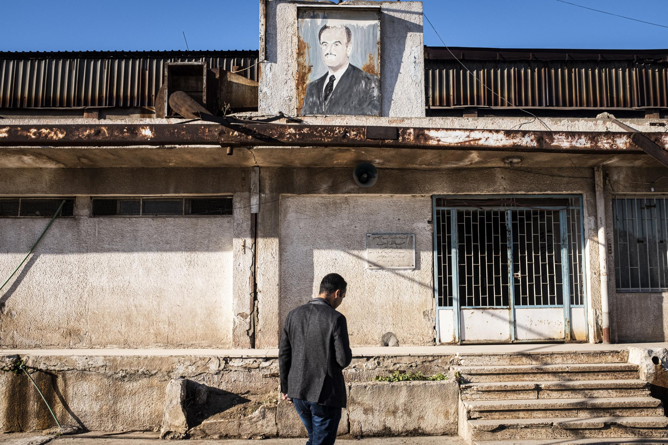 A man passing in front of a building with a Haffez Al Assad portrait. After the withdrawal of US troops from northern Syria in October 2019, Turkey launched an offensive against the predominantly Kurdish areas in the northeast of the country along Islamist forces. Calls for war crimes investigations into the conduct of Ankara-backed militias are mounting ever since. (Andoni Lubaki / Euskal Fondoa)