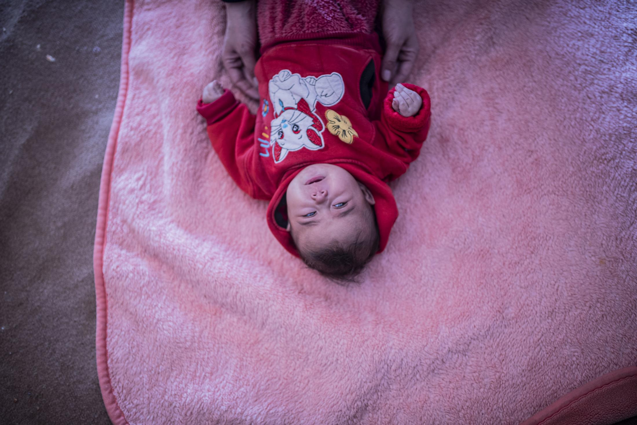 A newborn in Washokani refugee camp crying on the floor where her father has put a blanket to use it as a bed. After the withdrawal of US troops from northern Syria in October 2019, Turkey launched an offensive against the predominantly Kurdish areas in the northeast of the country along Islamist forces. Calls for war crimes investigations into the conduct of Ankara-backed militias are mounting ever since. (Andoni Lubaki / Euskal Fondoa)