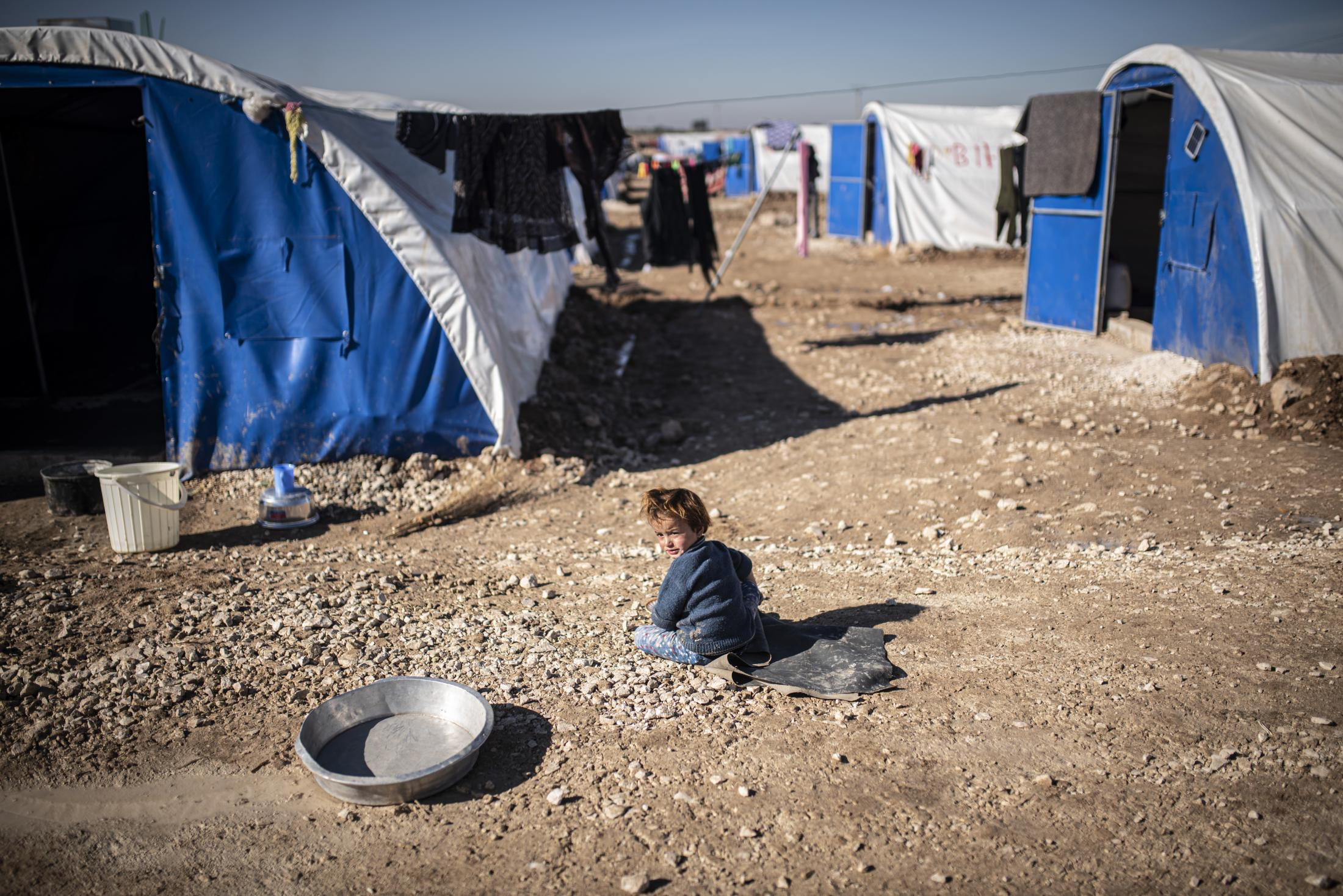 A child is playing outside the tent of her family in the Washokani refugee camp. After the withdrawal of US troops from northern Syria in October 2019, Turkey launched an offensive against the predominantly Kurdish areas in the northeast of the country along Islamist forces. Calls for war crimes investigations into the conduct of Ankara-backed militias are mounting ever since. (Andoni Lubaki / Euskal Fondoa)