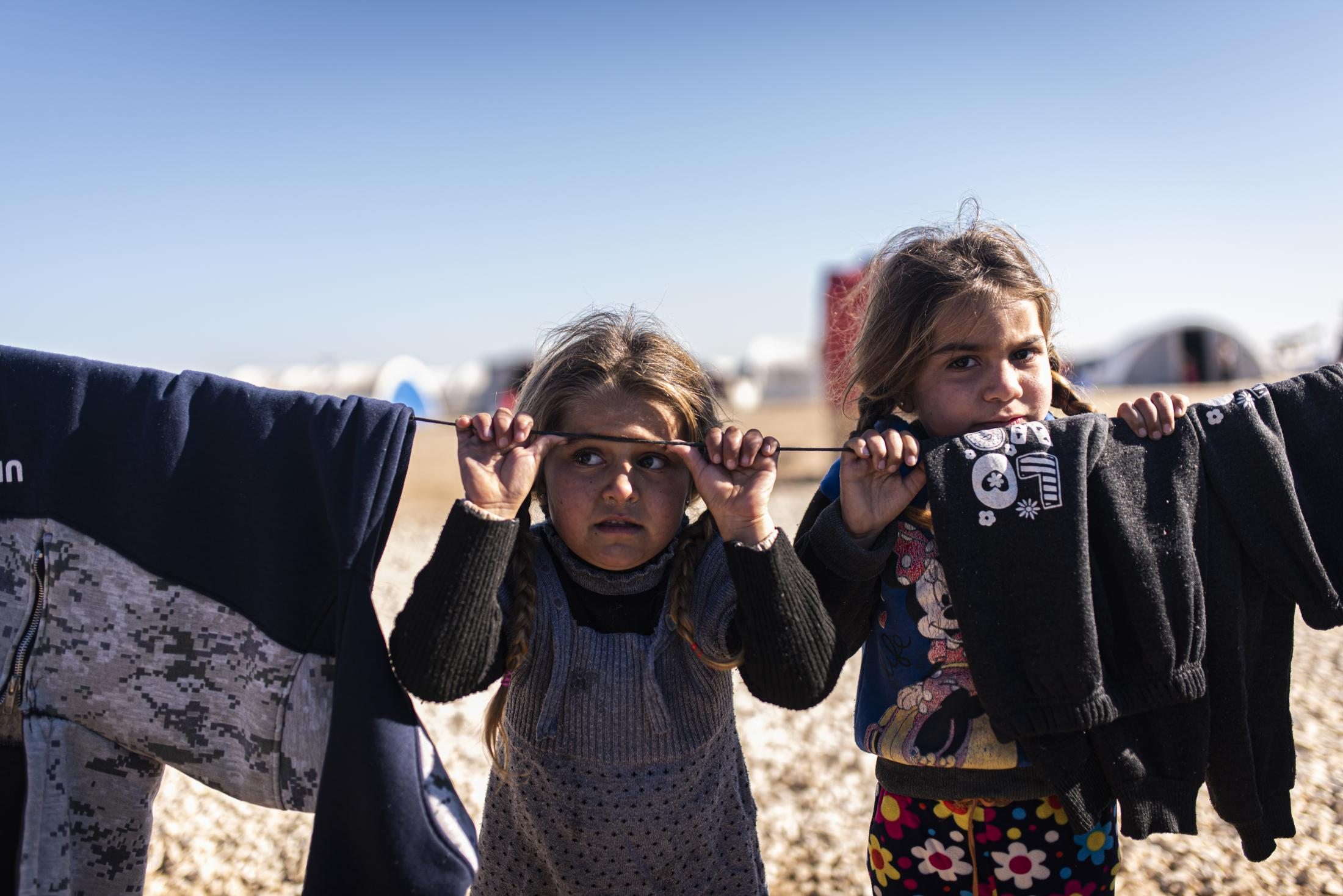 Children playing with a rope outside the tent of their family in the Washokani refugee camp. After the withdrawal of US troops from northern Syria in October 2019, Turkey launched an offensive against the predominantly Kurdish areas in the northeast of the country along Islamist forces. Calls for war crimes investigations into the conduct of Ankara-backed militias are mounting ever since. (Andoni Lubaki / Euskal Fondoa)