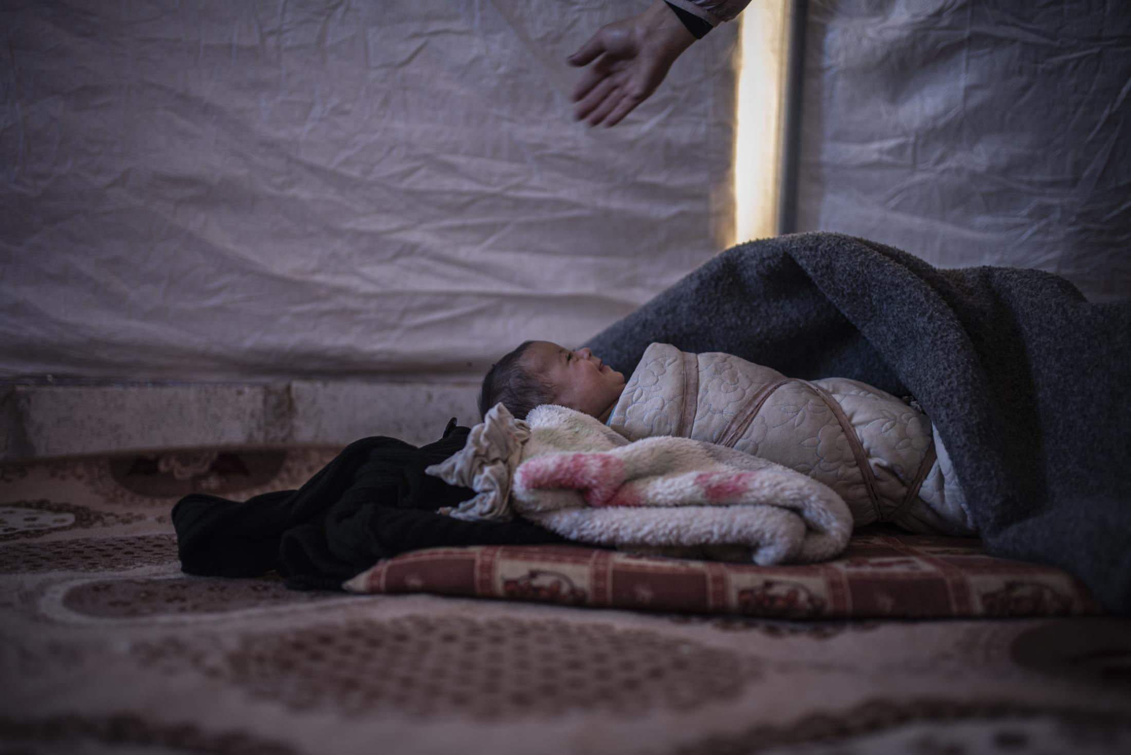 Ayah (6 months), a girl with Down Syndrome laughing with her aunt inside the tent of her family,who fleed from the outskirts of Serekaniye, in Washokani refugee camp. After the withdrawal of US troops from northern Syria in October 2019, Turkey launched an offensive against the predominantly Kurdish areas in the northeast of the country along Islamist forces. Calls for war crimes investigations into the conduct of Ankara-backed militias are mounting ever since. (Andoni Lubaki / Euskal Fondoa)